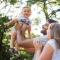 parents tossing toddler in air and laughing