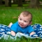 baby boy laughing on blanket in grass