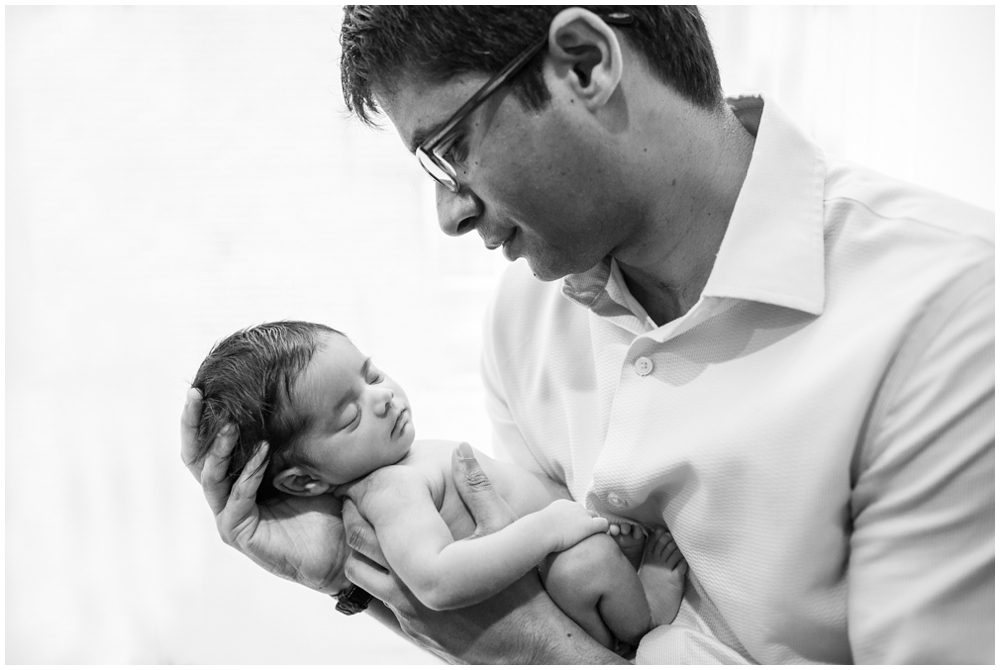 dad with newborn baby girl in home
