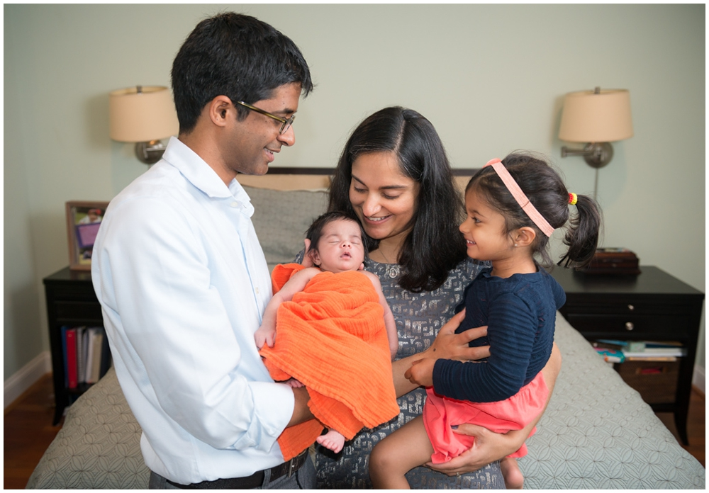 parents and sister with newborn baby girl in home