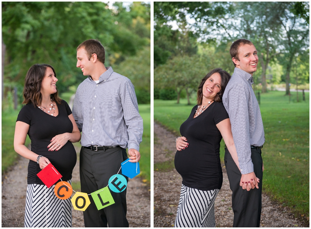 pregnant couple in park with banner