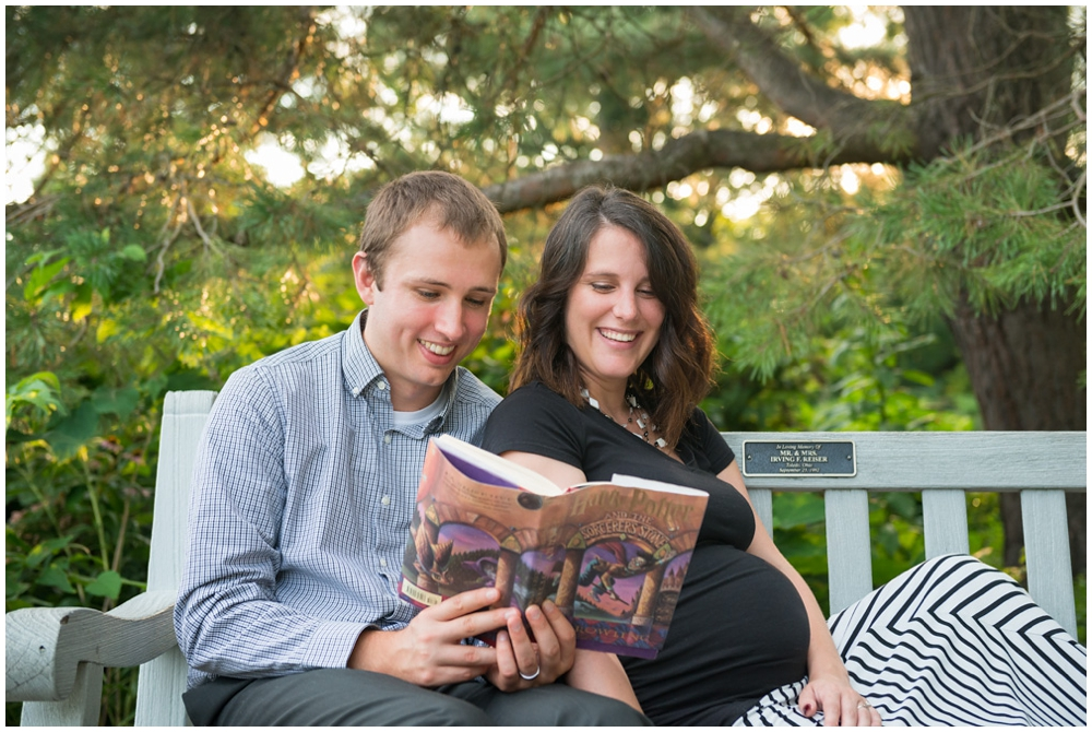 pregnant couple reading Harry Potter book on park bench