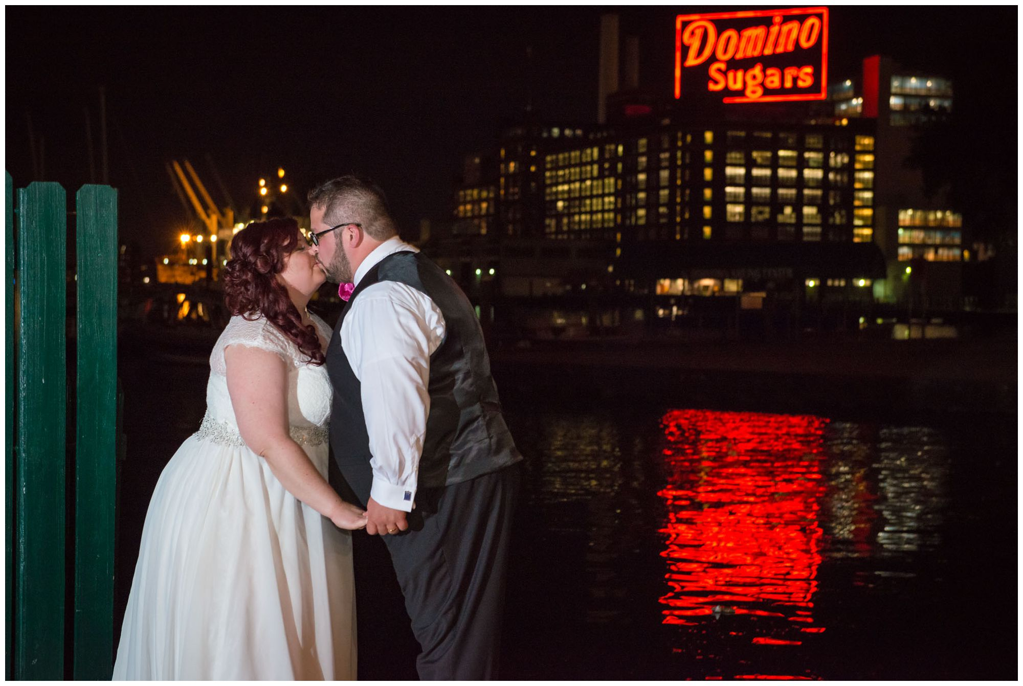 Bride and groom at nighttime in front of Domino Sugar factory in Baltimore