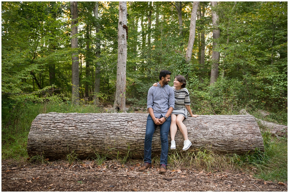 Engaged couple on large log at Green Spring Gardens in Alexandria, Virginia