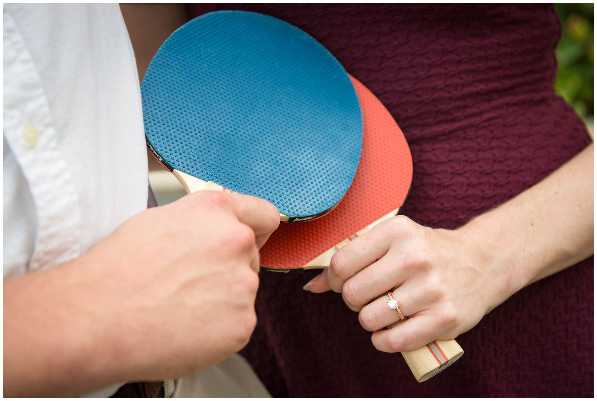 engaged couple playing ping pong in urban park