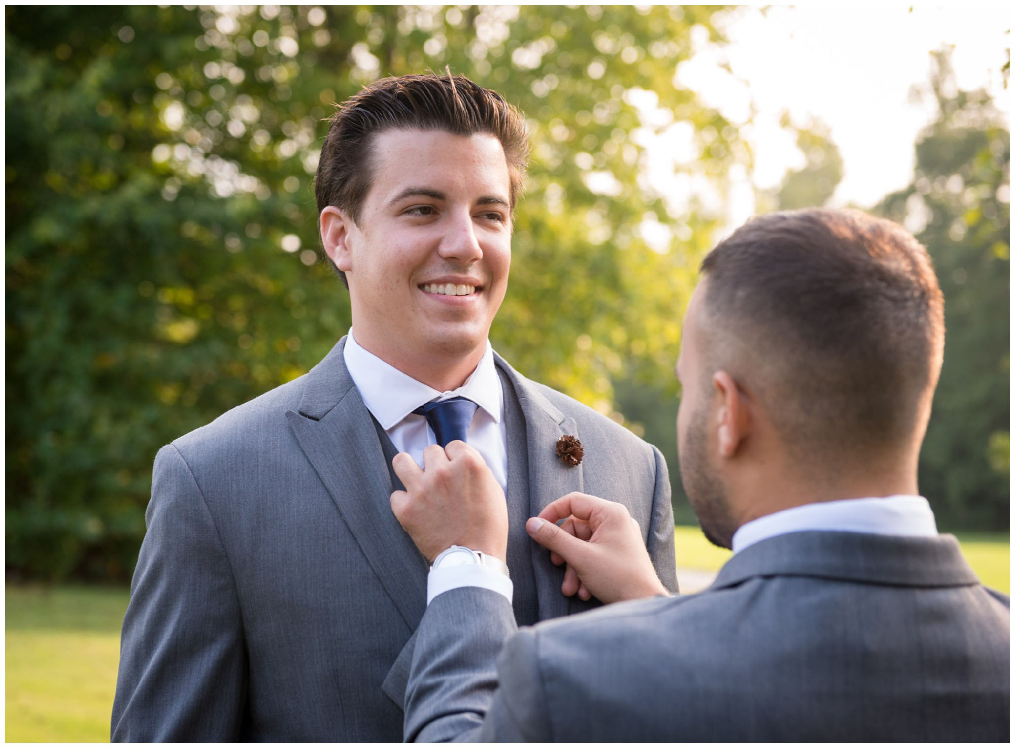 groom tying tie before wedding