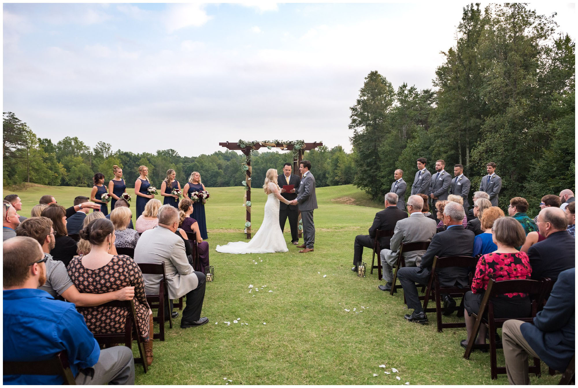 bride and groom holding hands during wedding ceremony on golf course