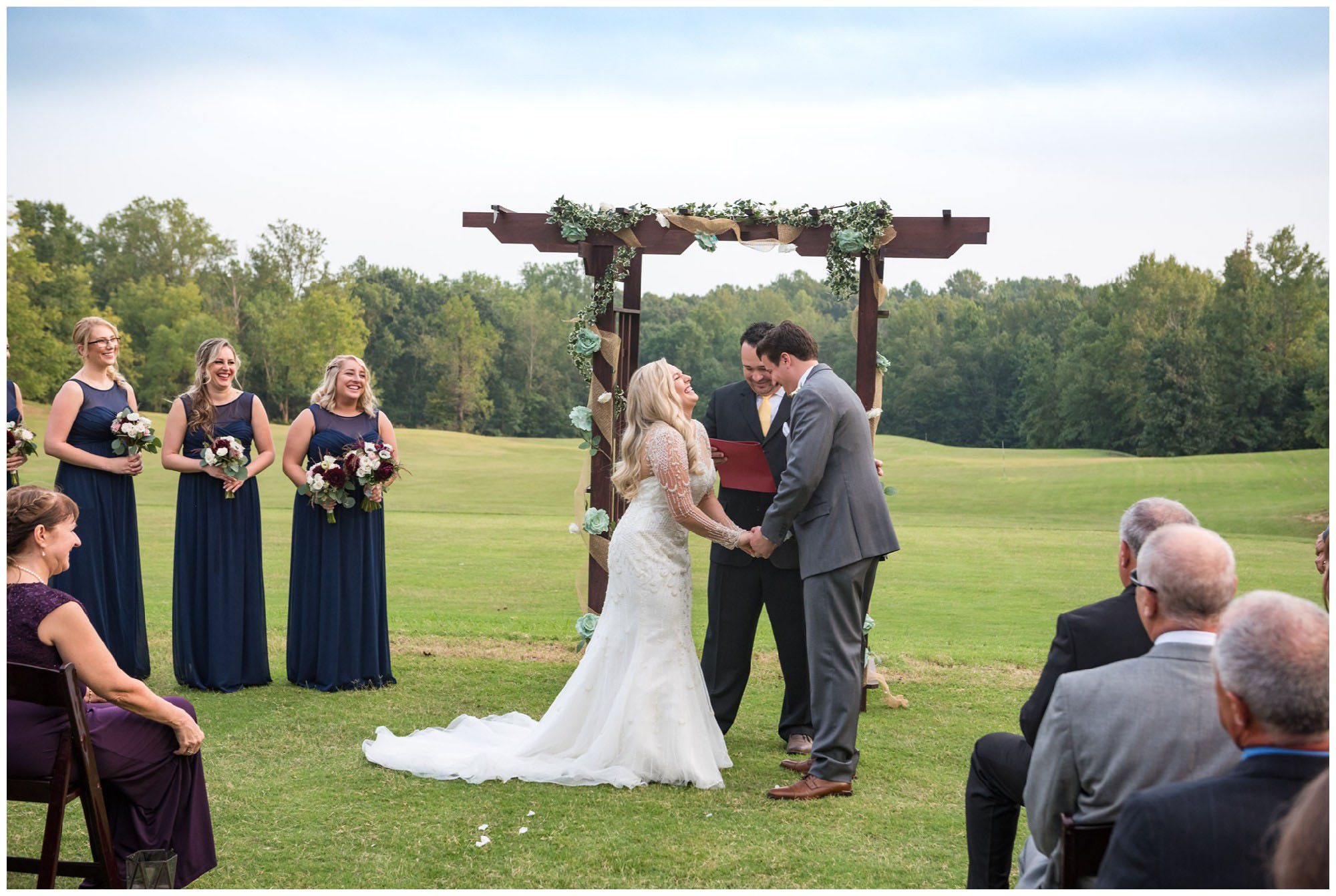bride and groom laughing during wedding ceremony on golf course