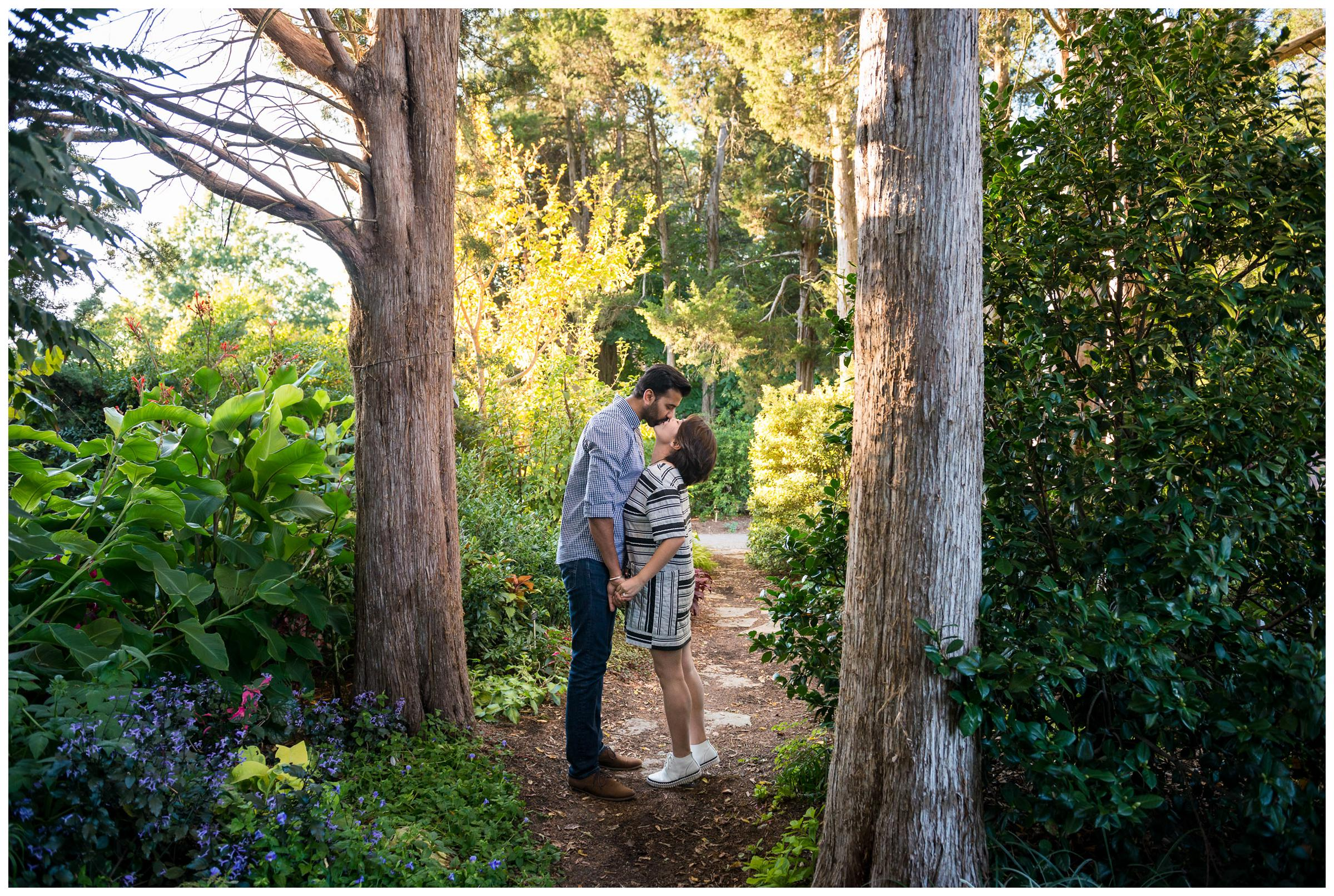 engaged couple kissing in forest