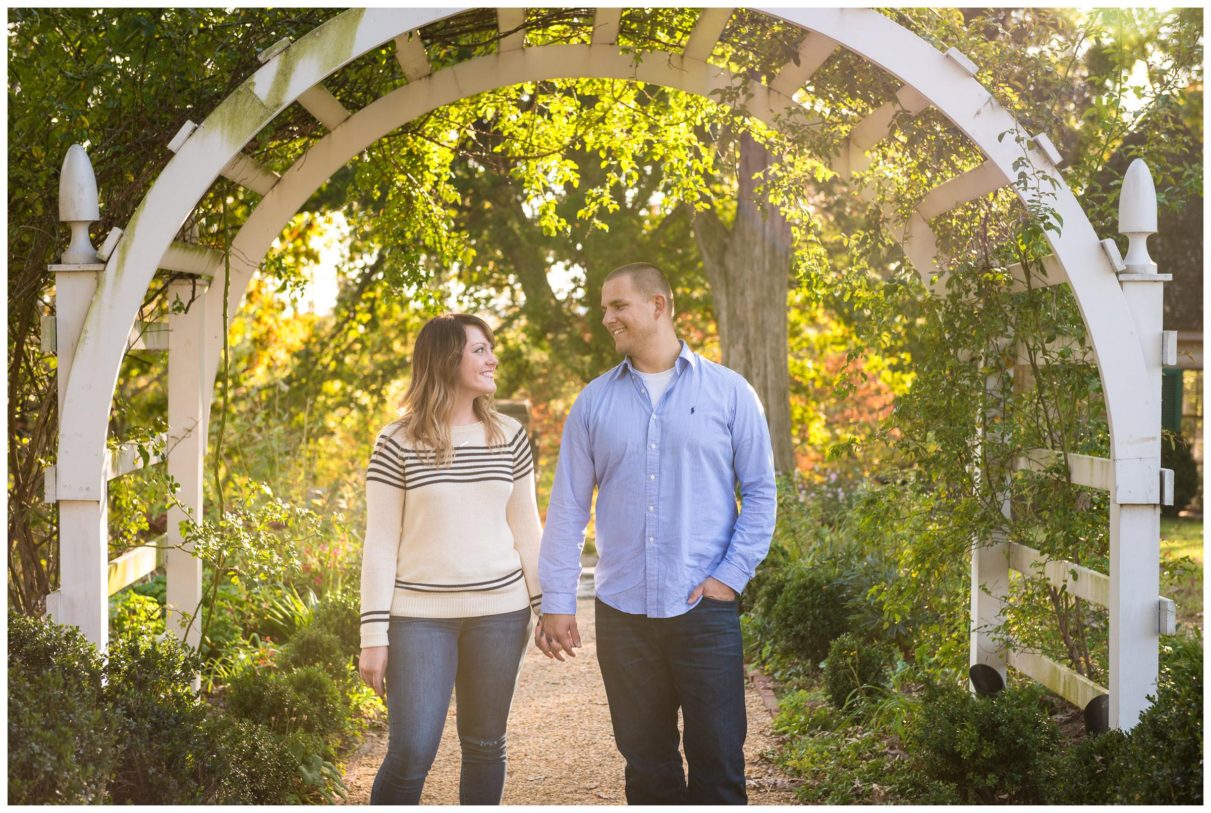 engaged couple under archway with sun flare