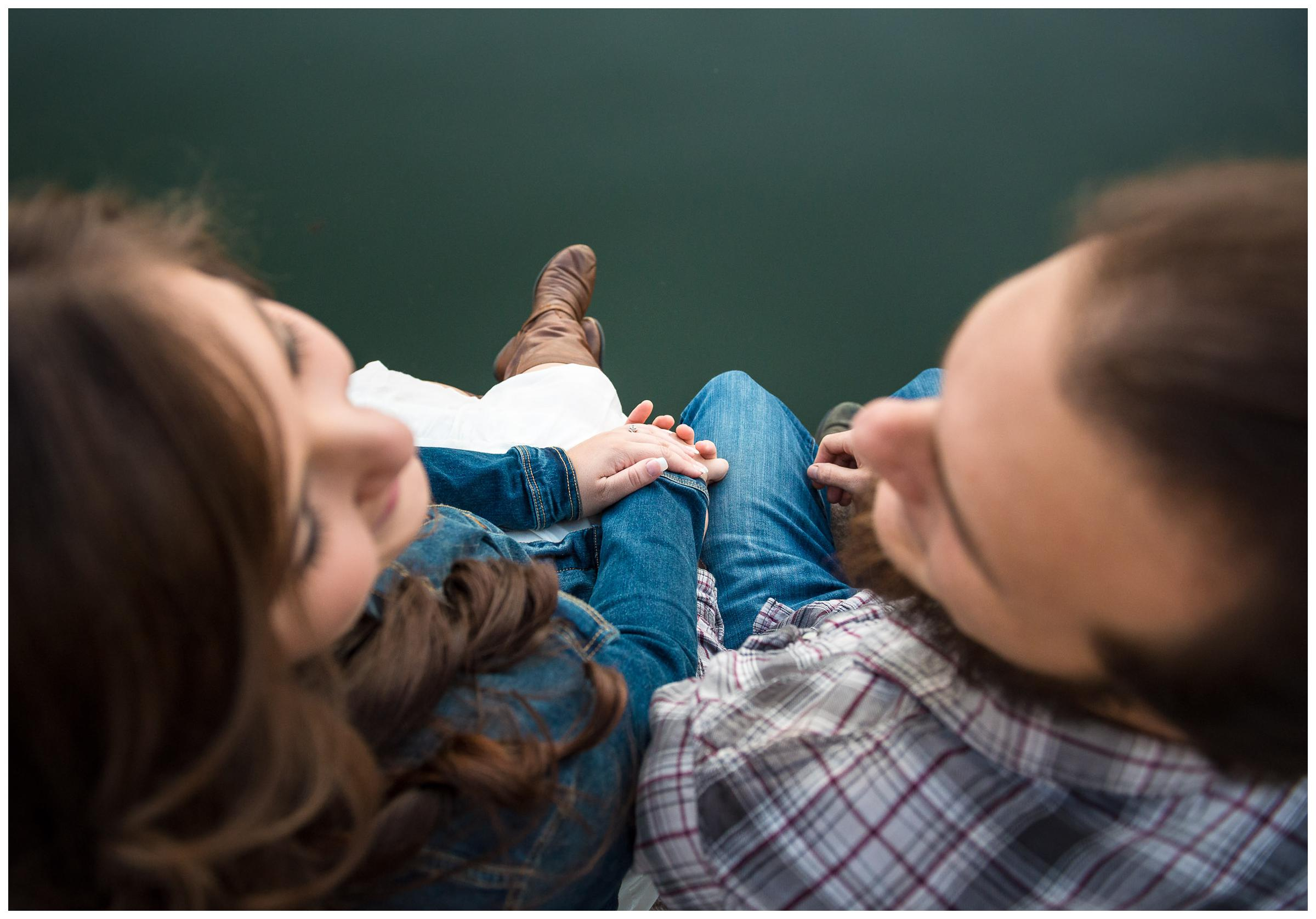engaged couple sitting on dock by river