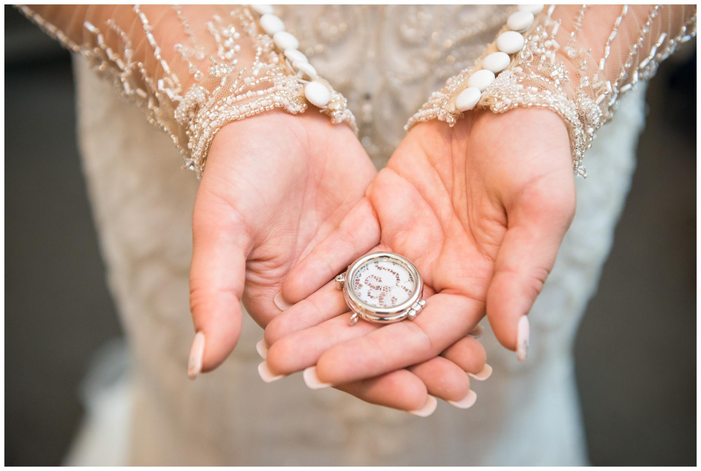 bride holding locket of mother's lace