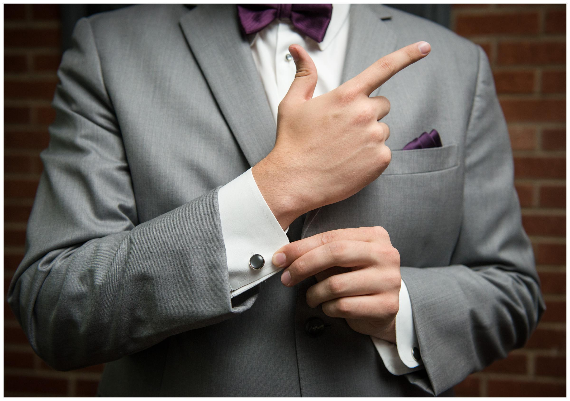 detail of groom's cufflinks while he makes James Bond gesture