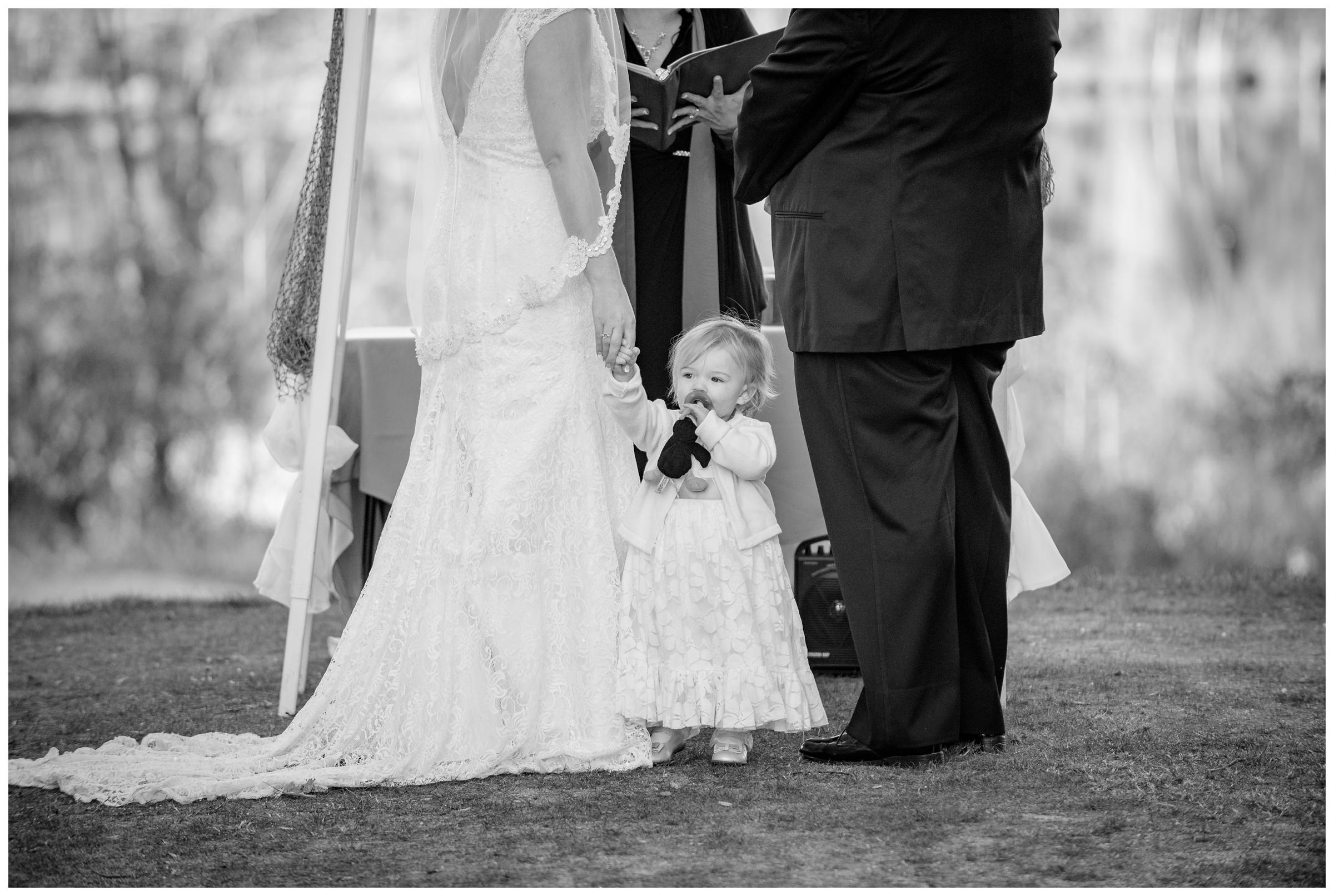 bride and groom's daughter standing with them during wedding ceremony