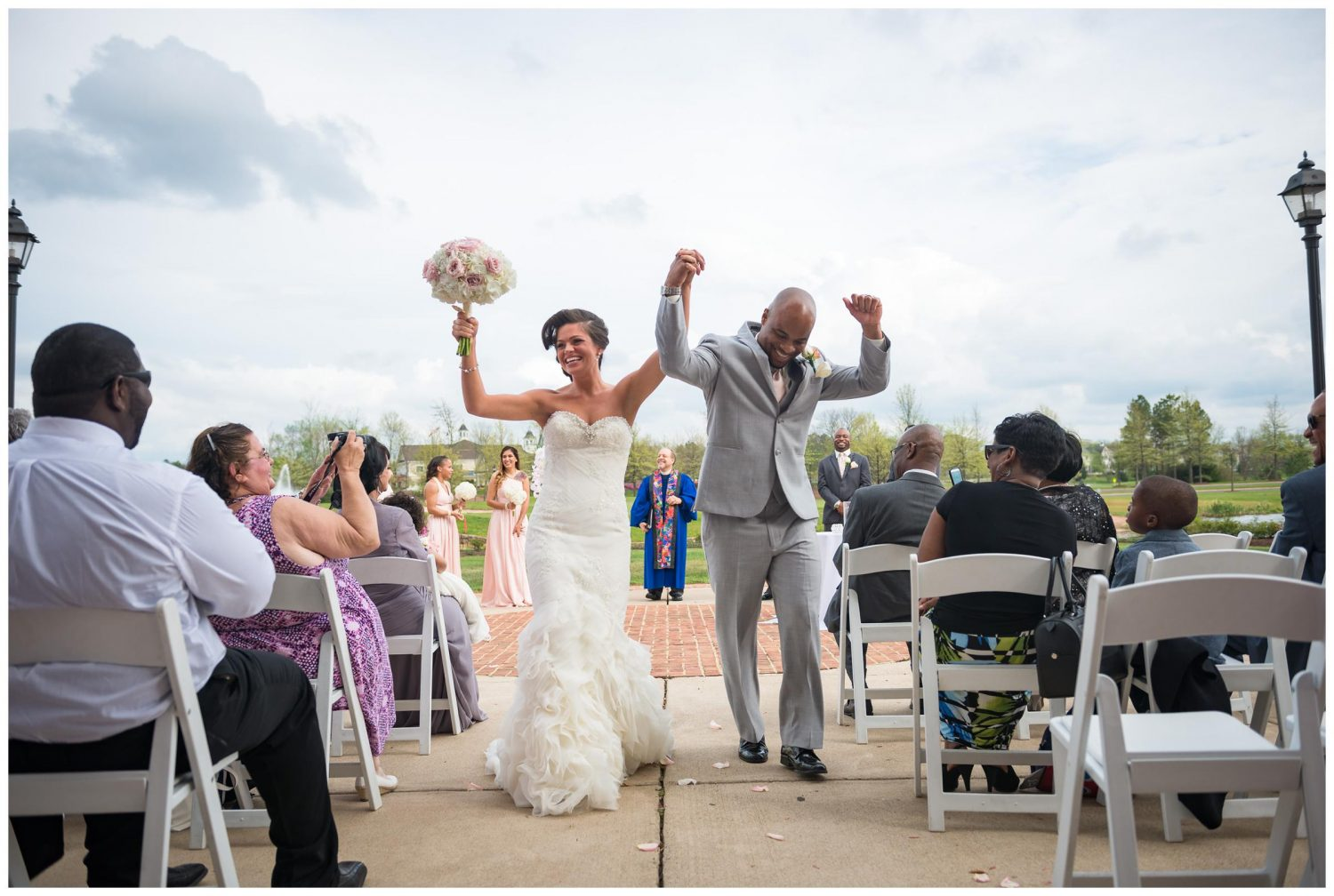 bride and groom cheering during wedding recessional