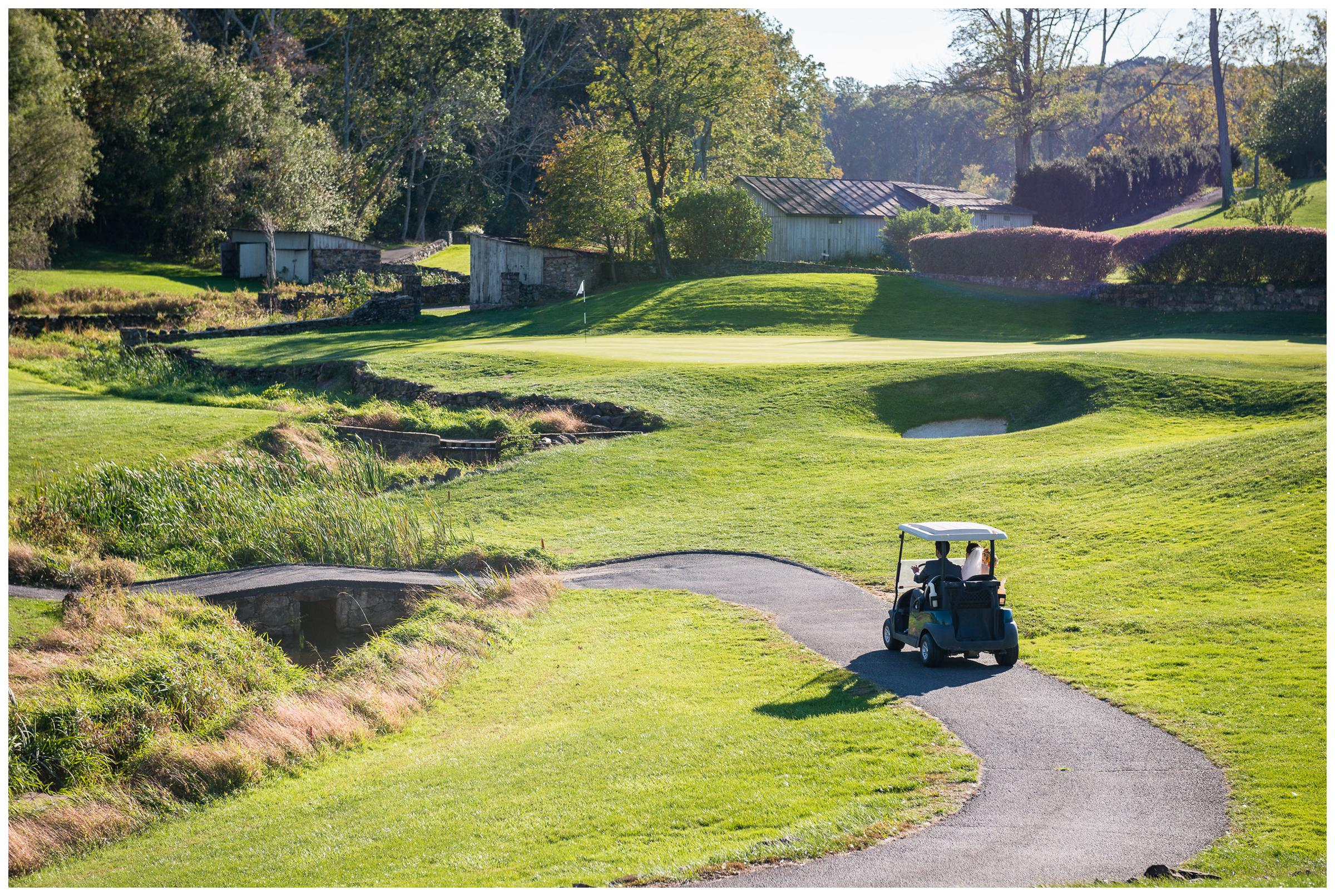 bride and groom ride in golf cart across green