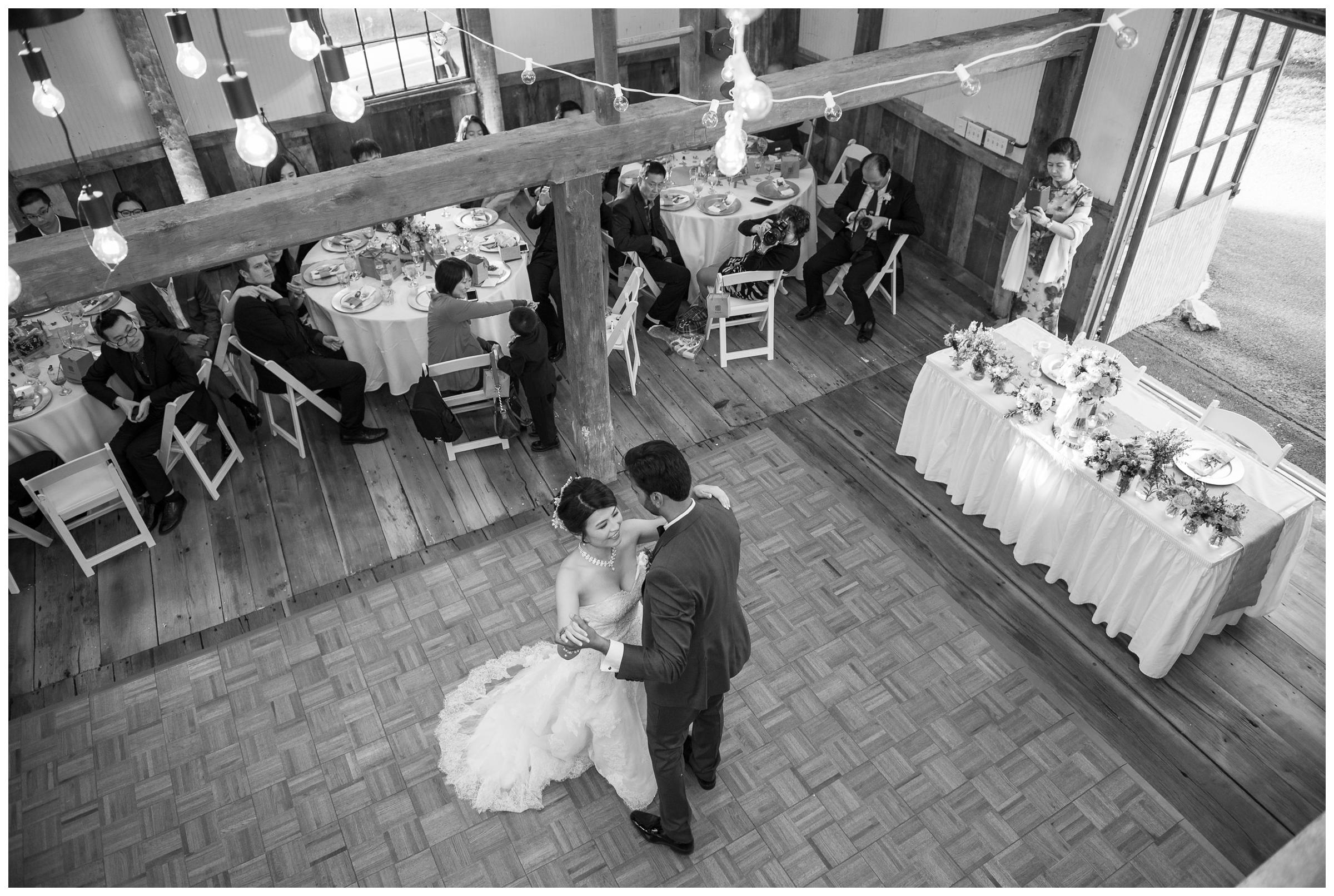 bride and groom share first dance in barn reception
