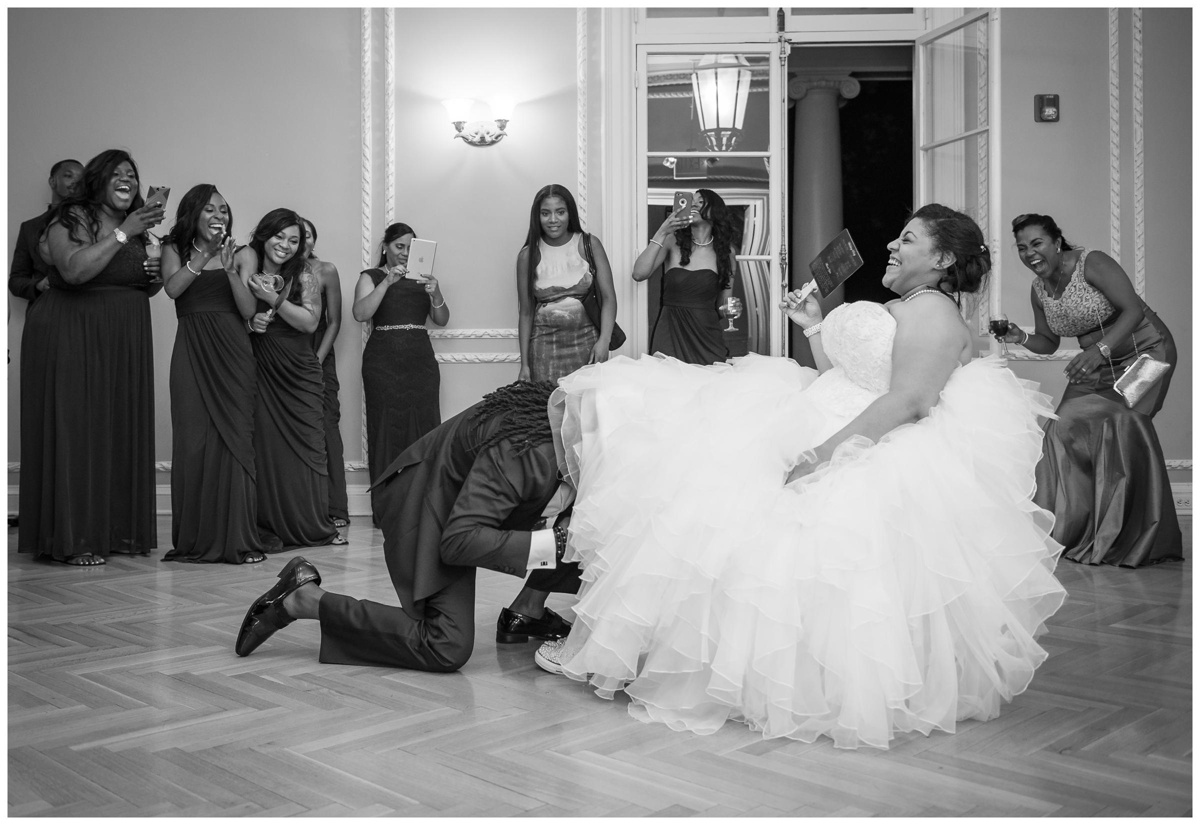 groom retrieving garter while guests laugh