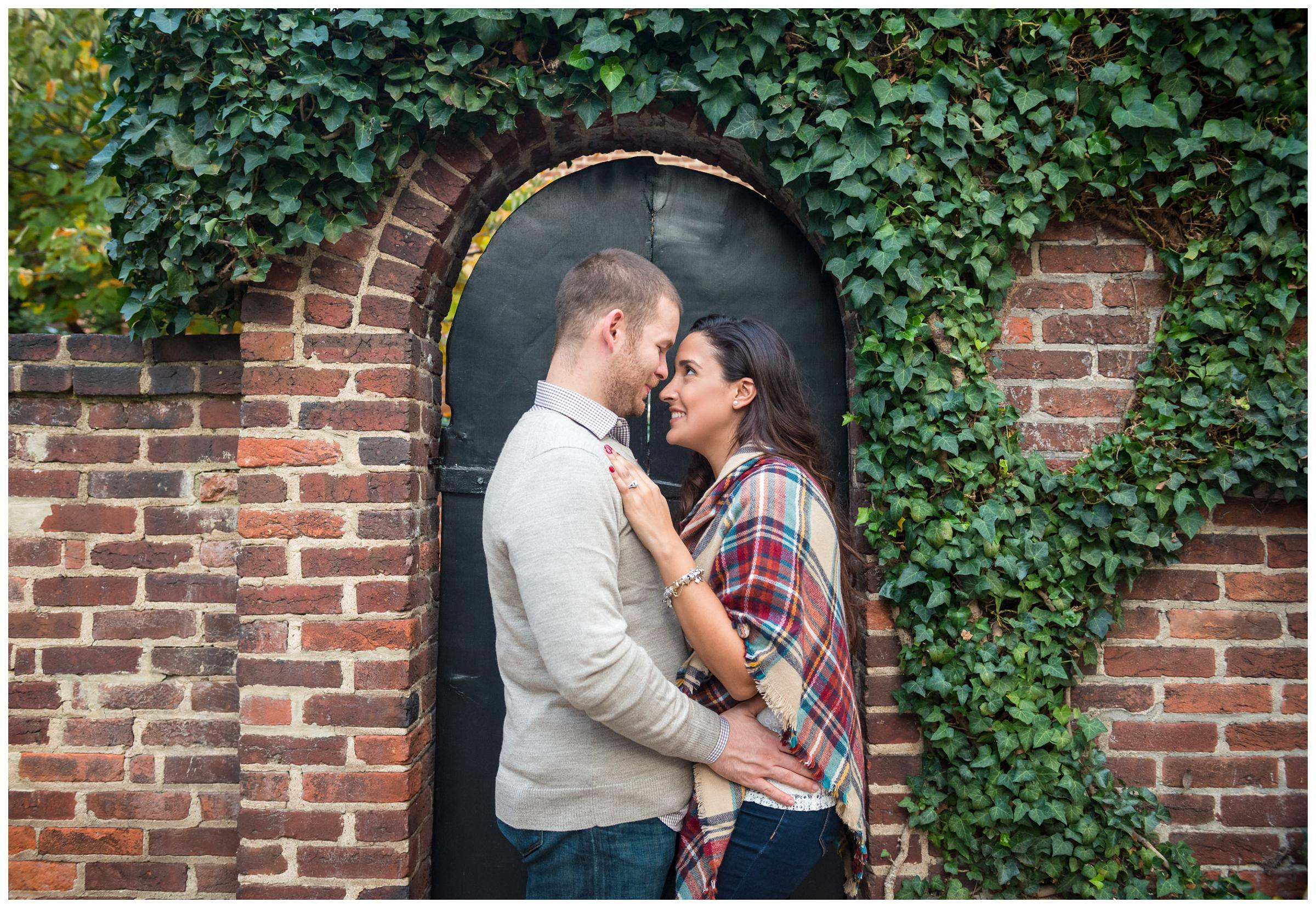 engaged couple in front of brick wall and archway surrounded by vines
