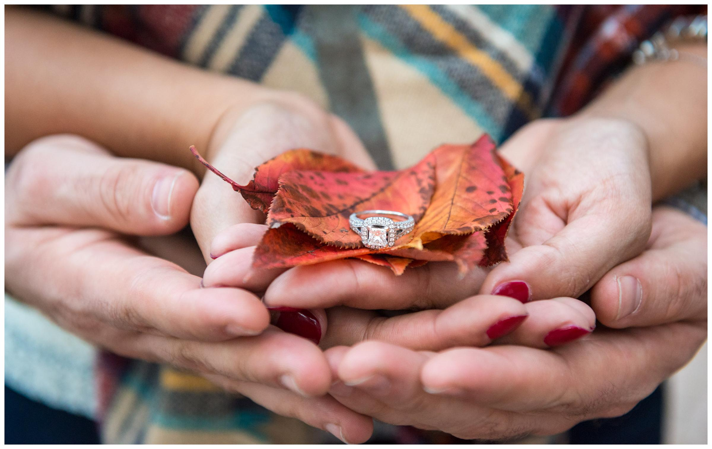 closeup of engagement ring and fall leaves