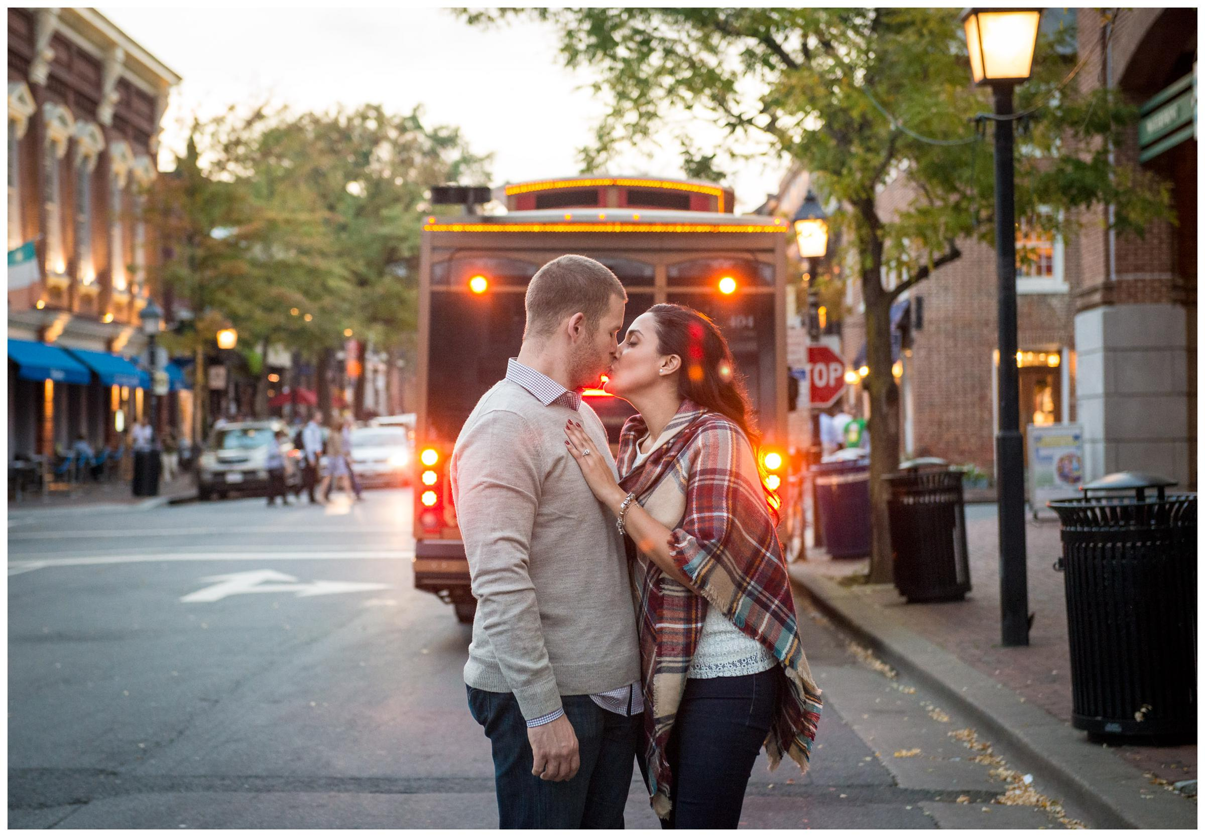 engaged couple kissing in front of historic trolley in Alexandria, Virginia