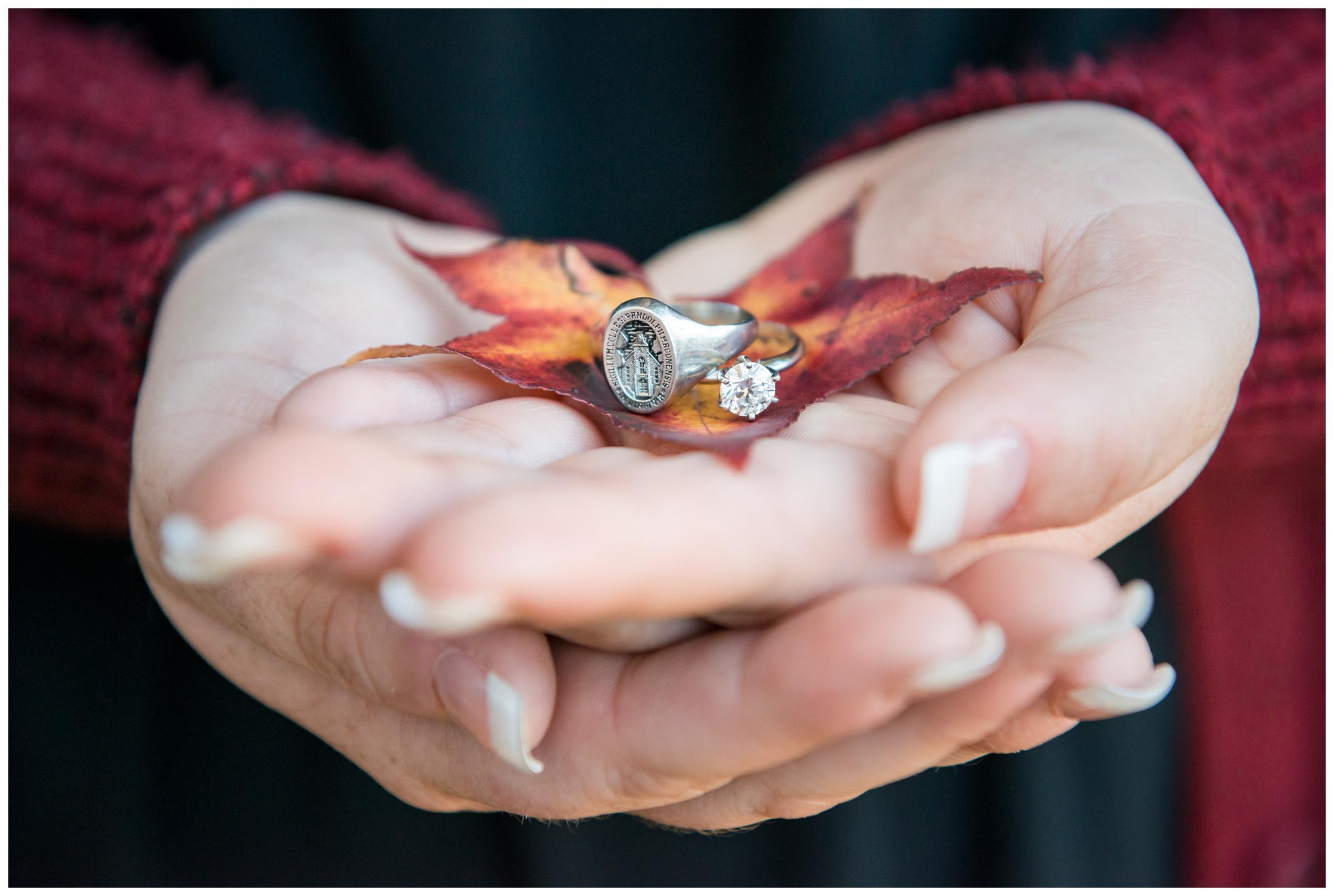 Bride-to-be holding engagement ring and Randolph-Macon class ring with fall leaves.