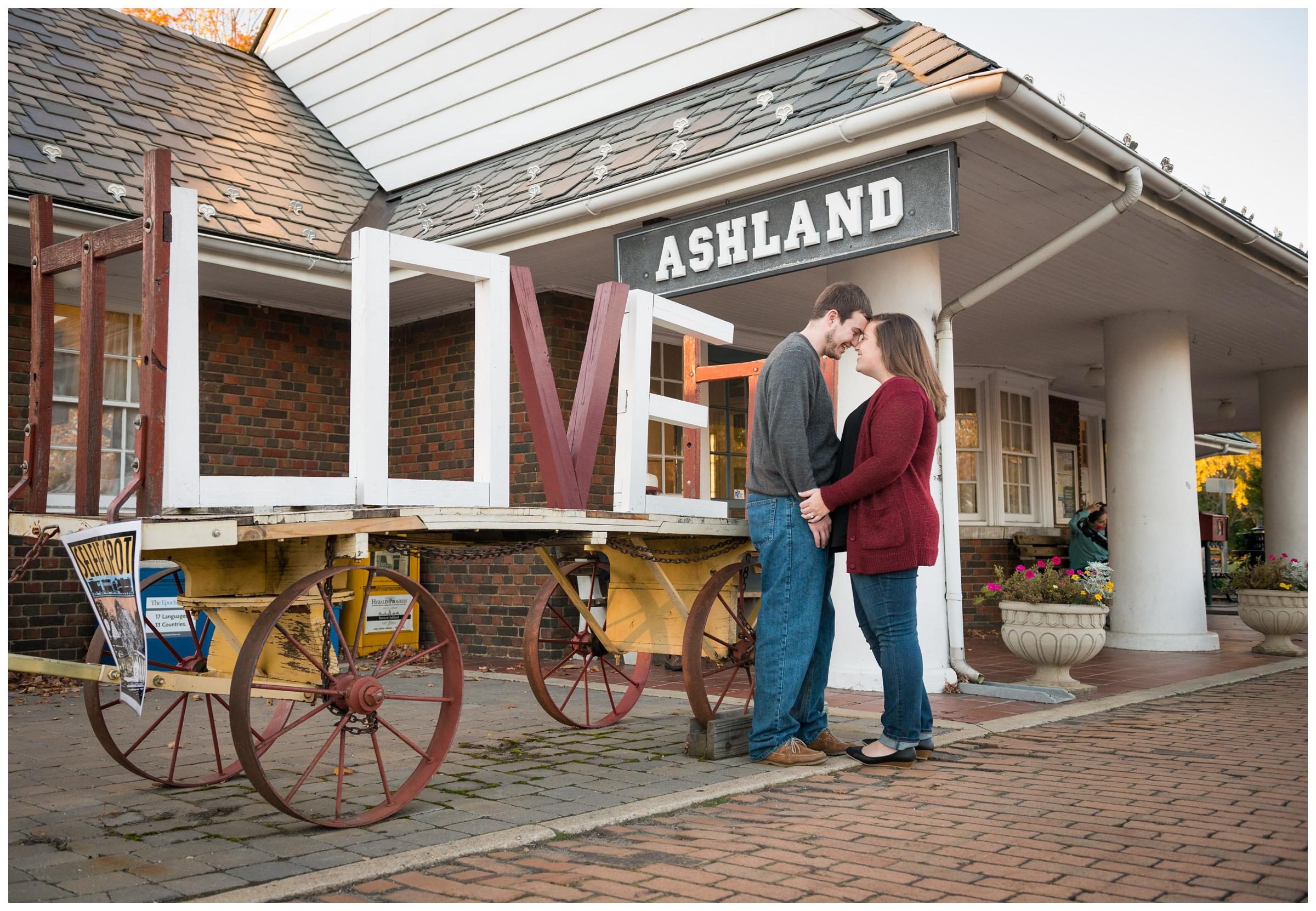 Engagement photos with LOVE sign near train station in Ashland, Virginia.