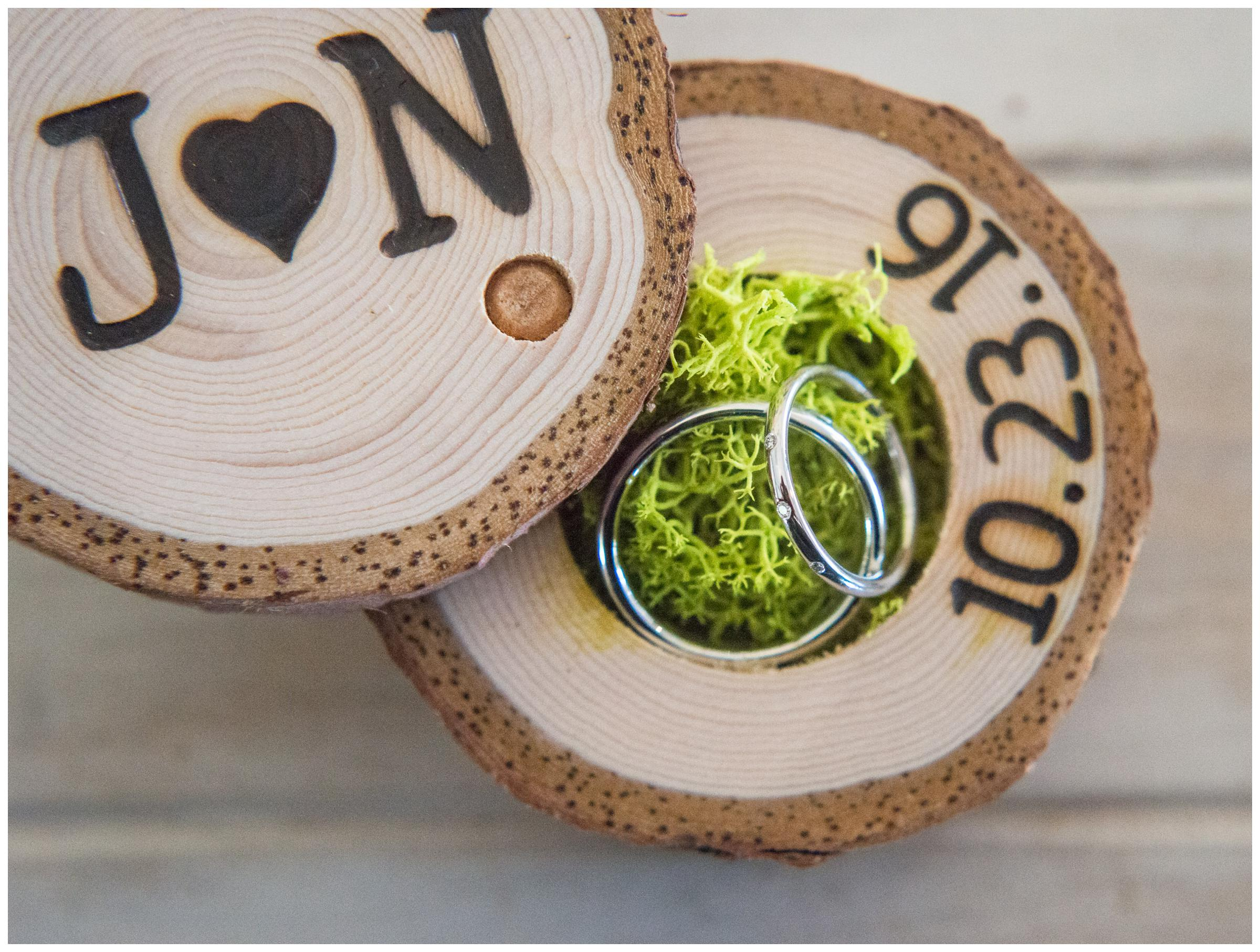 Rustic engraved wooden ring box with moss and wedding bands.