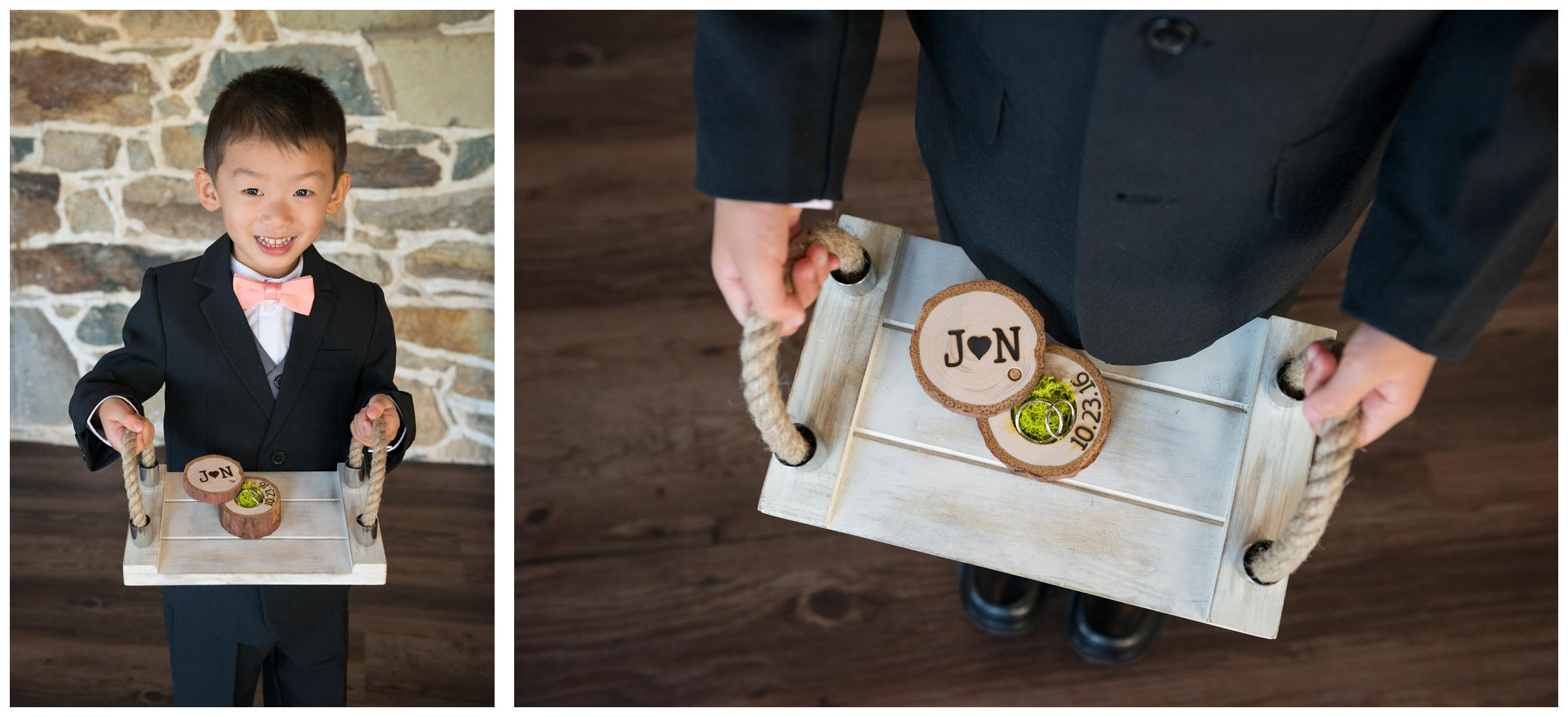 Ring bearer holding rustic wooden ring box on wooden tray.