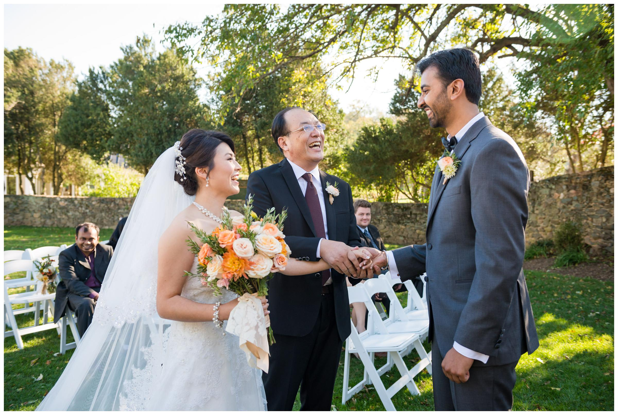 Father giving daughter away to groom during rustic wedding ceremony.