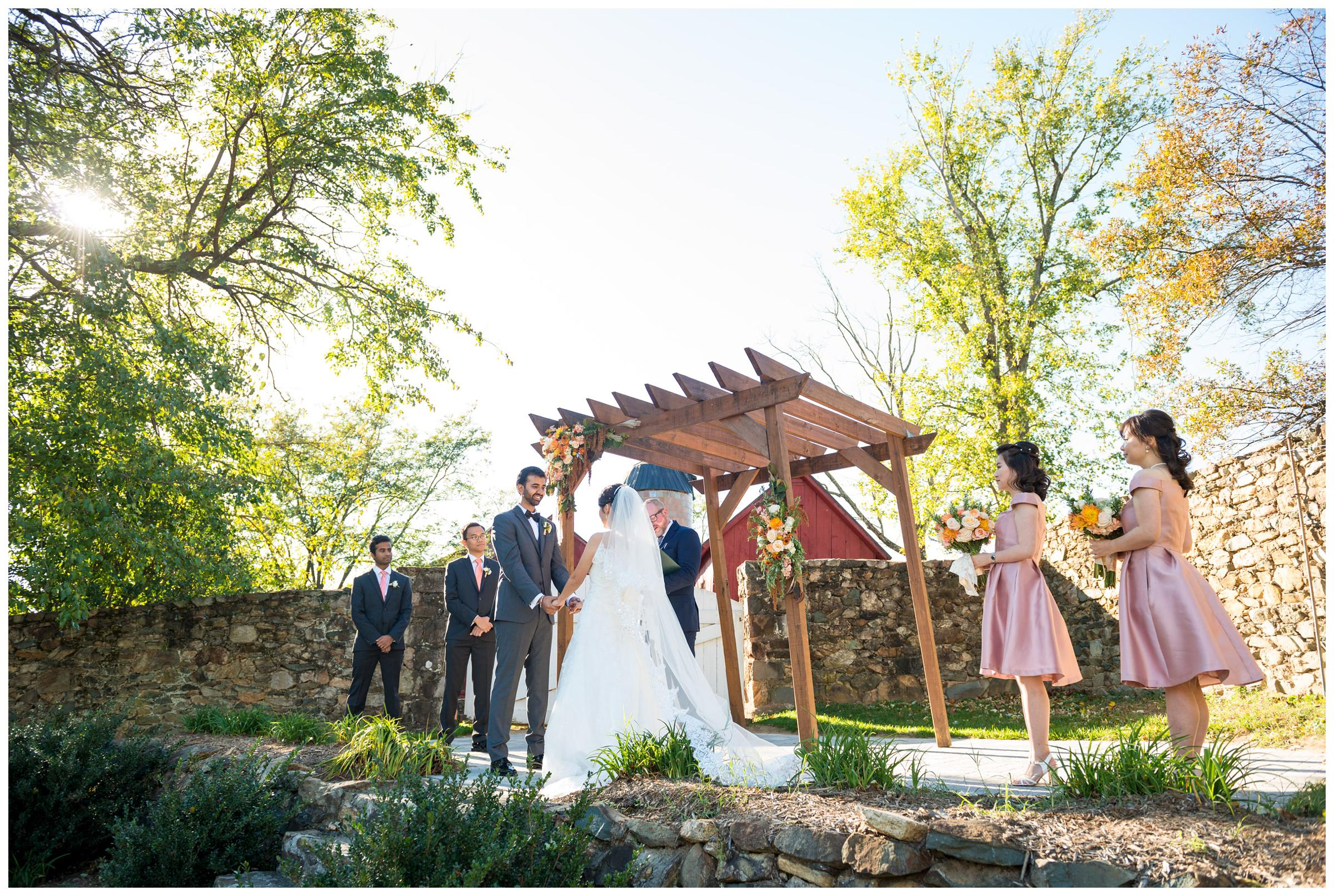 Bride and groom with bridal party during rustic fall wedding ceremony at Stoneleigh Golf Club in Virginia