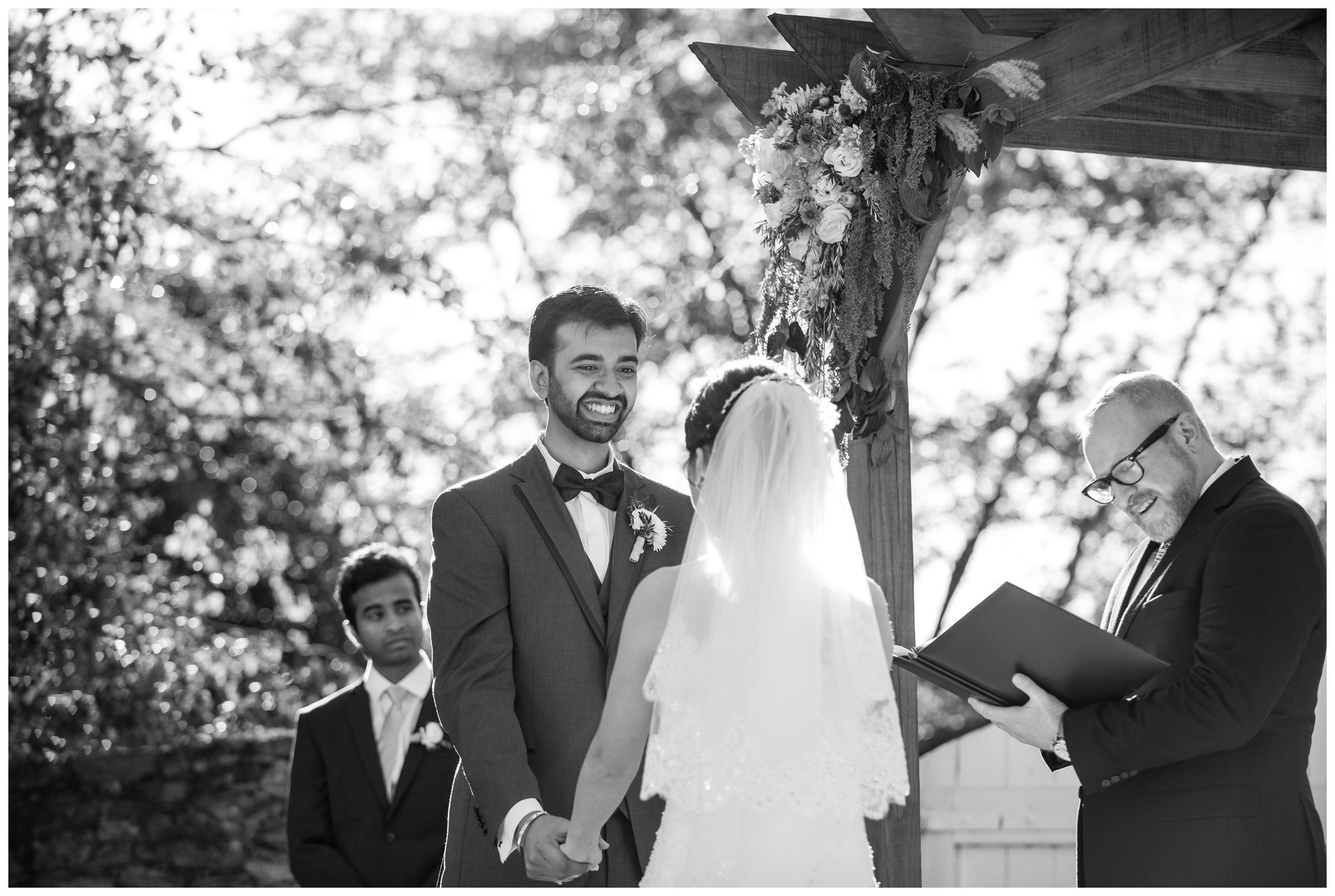 Groom smiling during rustic outdoor wedding ceremony.