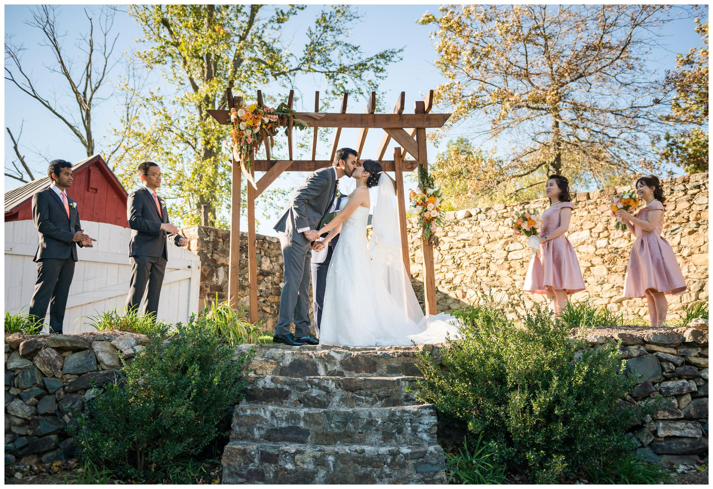 Bride and groom's first kiss during rustic wedding ceremony at Stoneleigh Golf Club in Round Hill, Virginia.