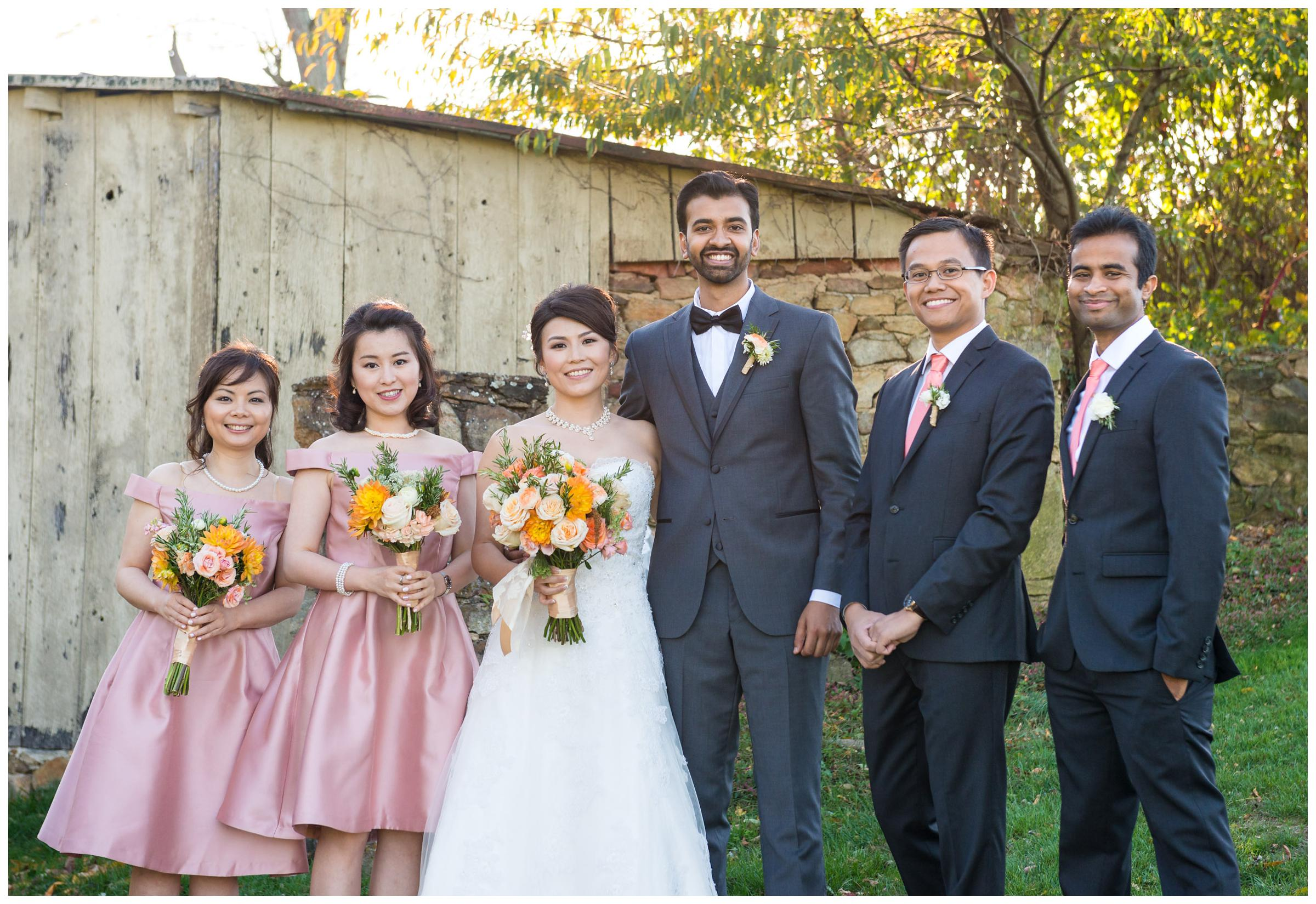 Portrait of bridal party near stone ruins at rustic wedding.