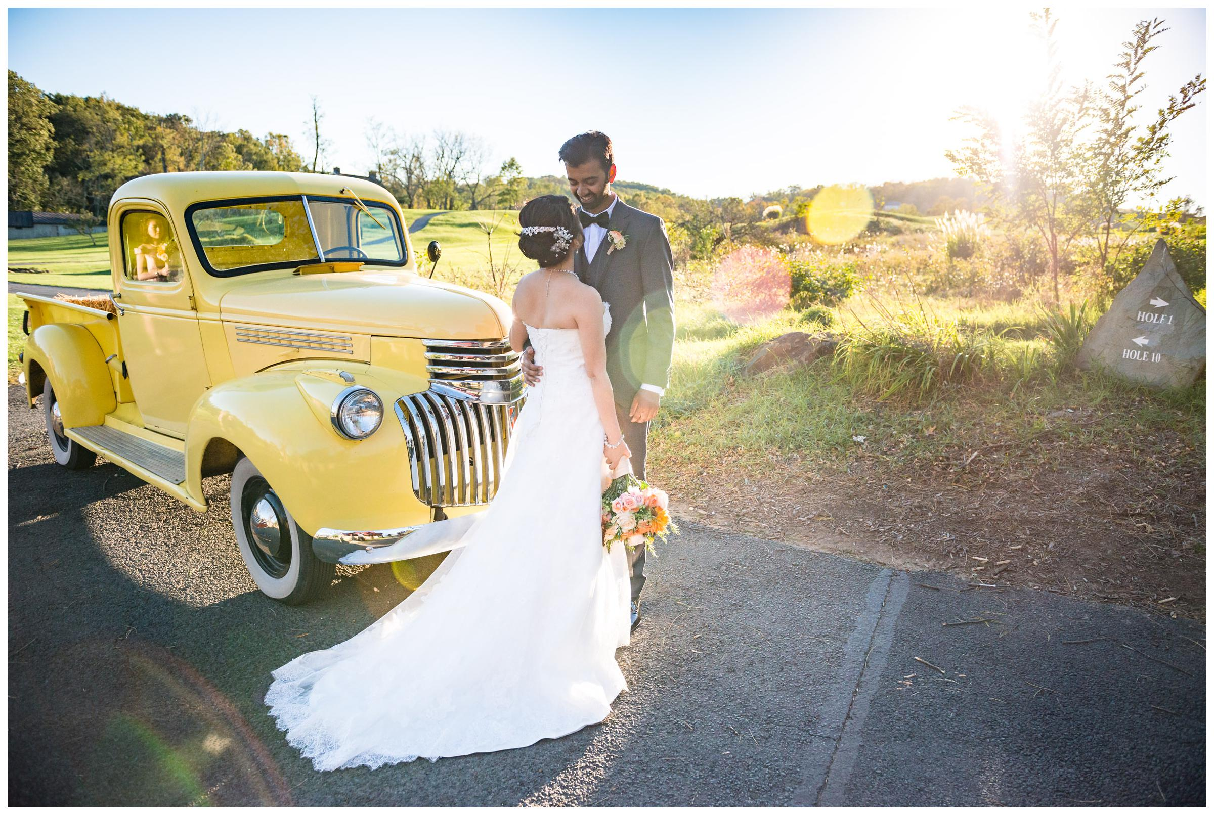 Portrait of bride and groom with vintage yellow truck during wedding at Stoneleigh Golf Club in Round Hill, Virginia.