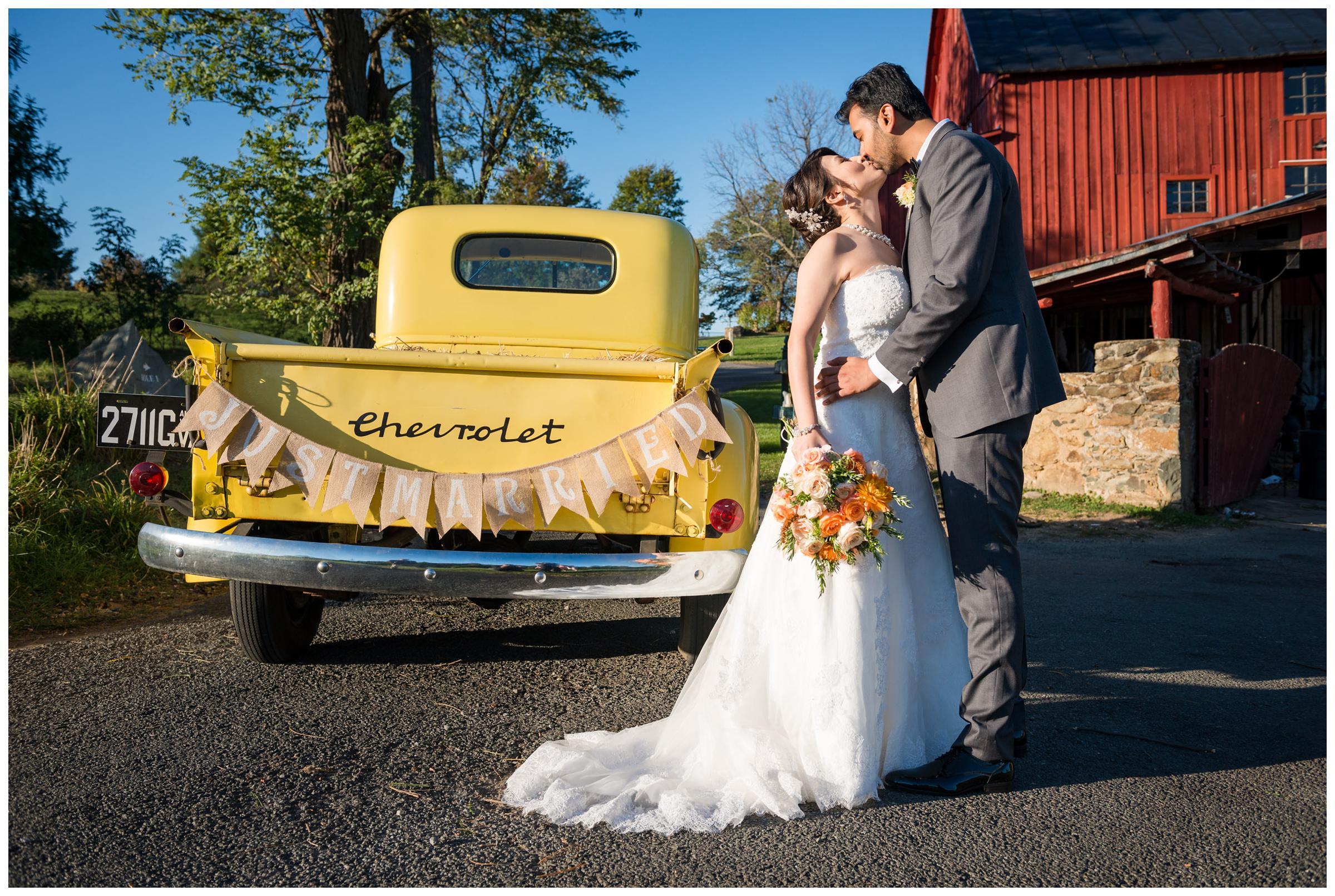 "Bride and groom with vintage yellow Chevrolet truck with ""just married"" banner"