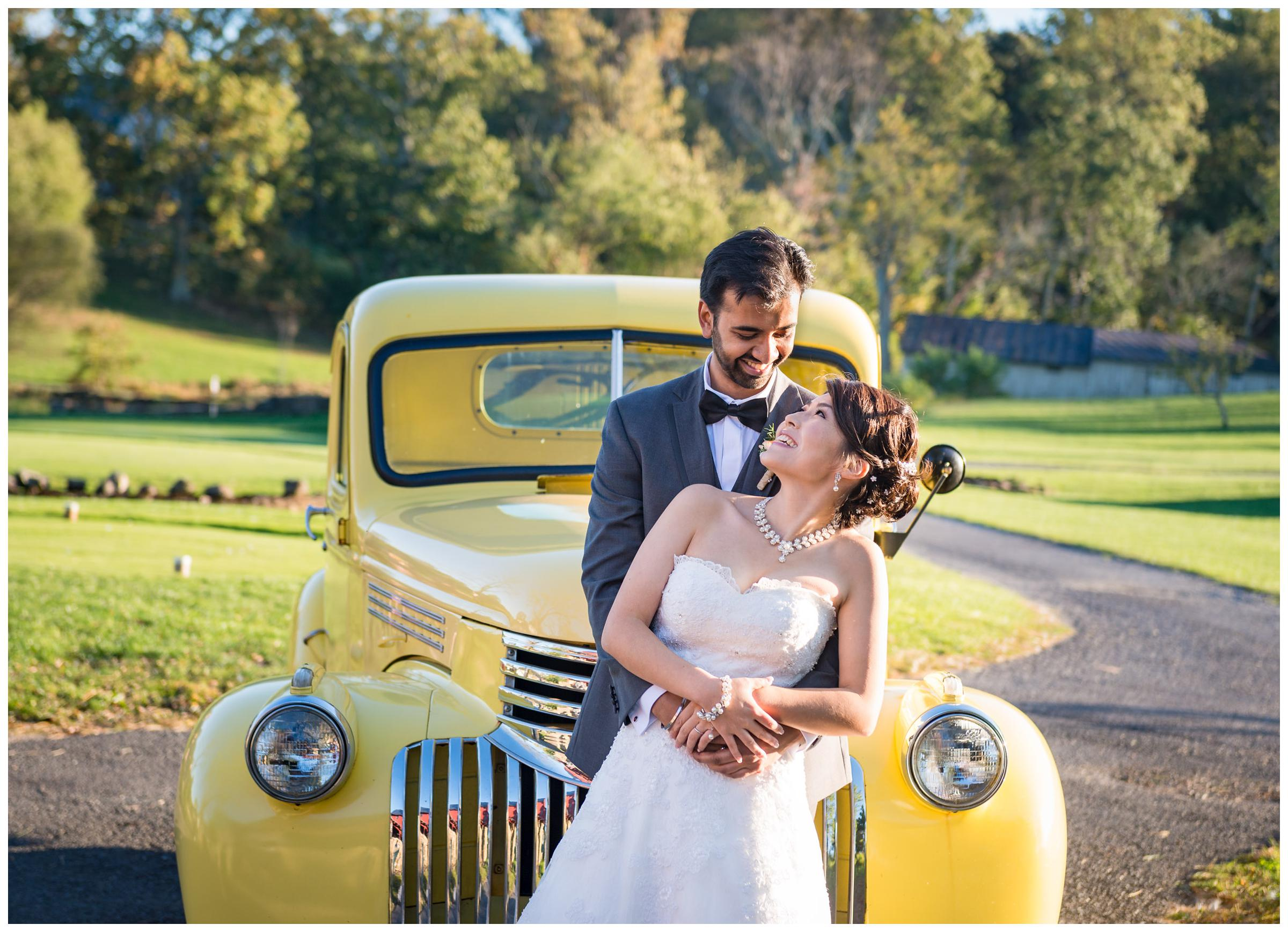 Bride and groom with vintage yellow truck during rustic wedding at Stoneleigh Golf Club