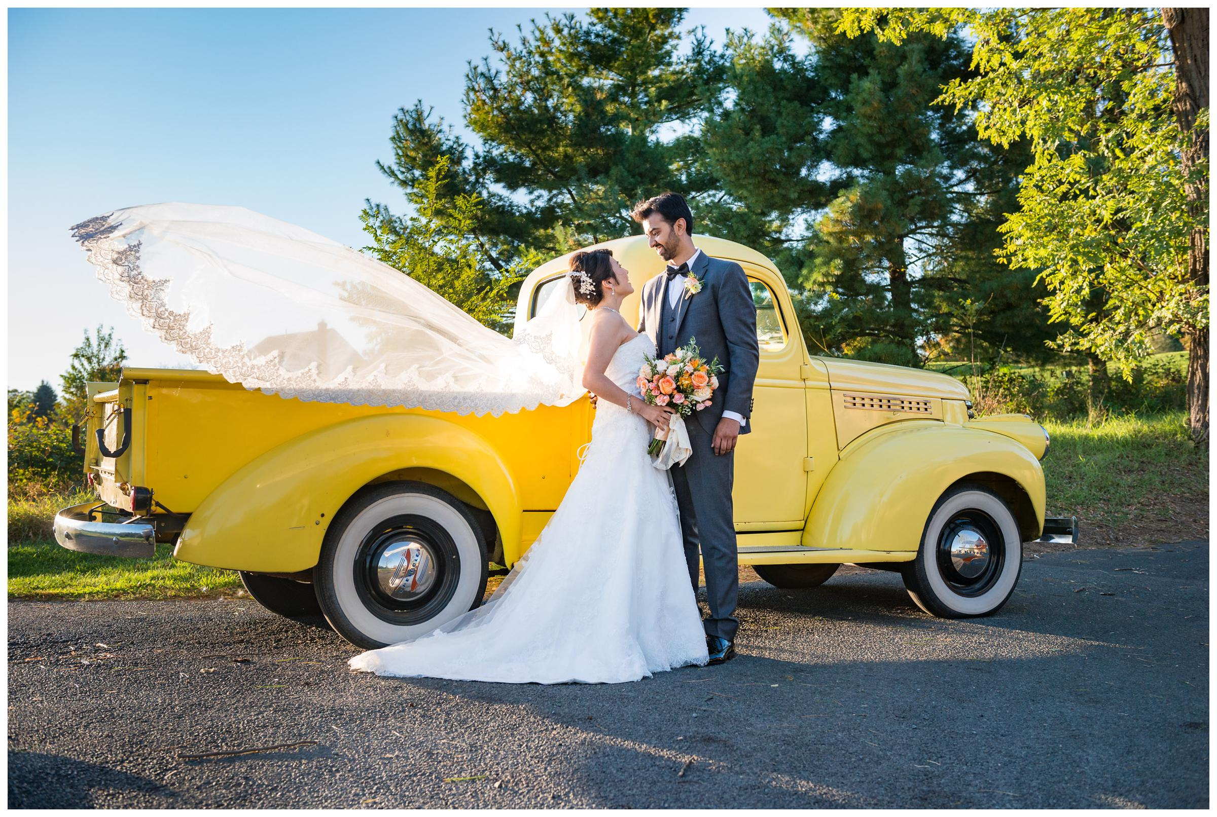 Bride and groom with vintage yellow truck and veil blowing in wind.