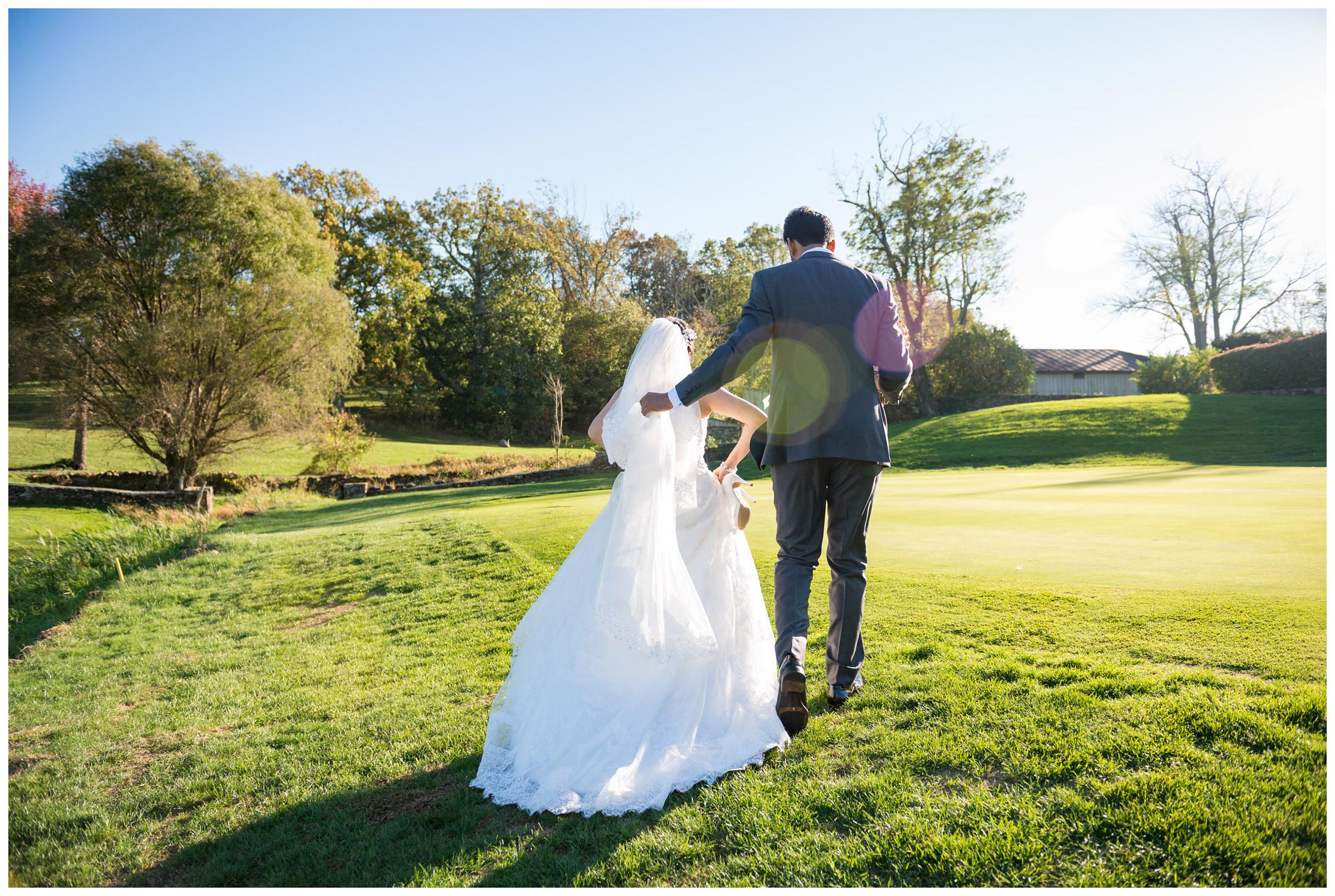 Groom helping bride up hillside at Stoneleigh Golf Club