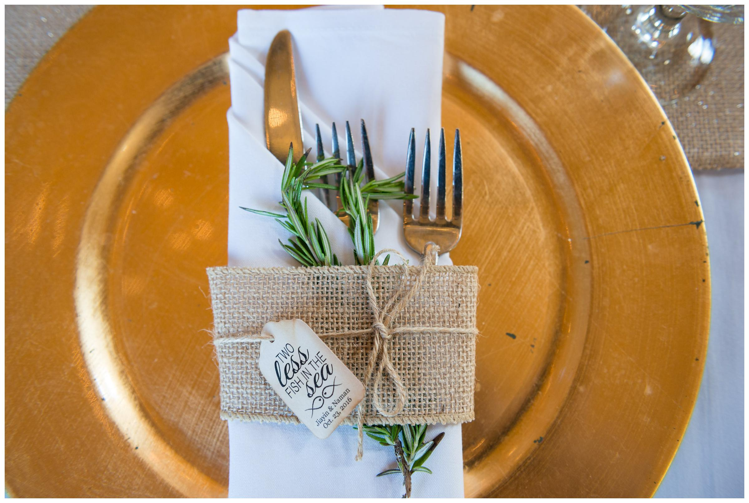 Rustic gold and burlap reception place settings with herbs.