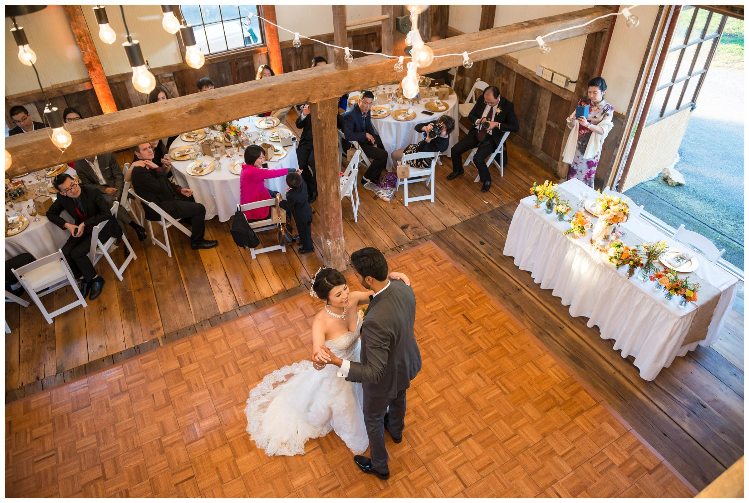 Bride and groom have their first dance during rustic barn reception.