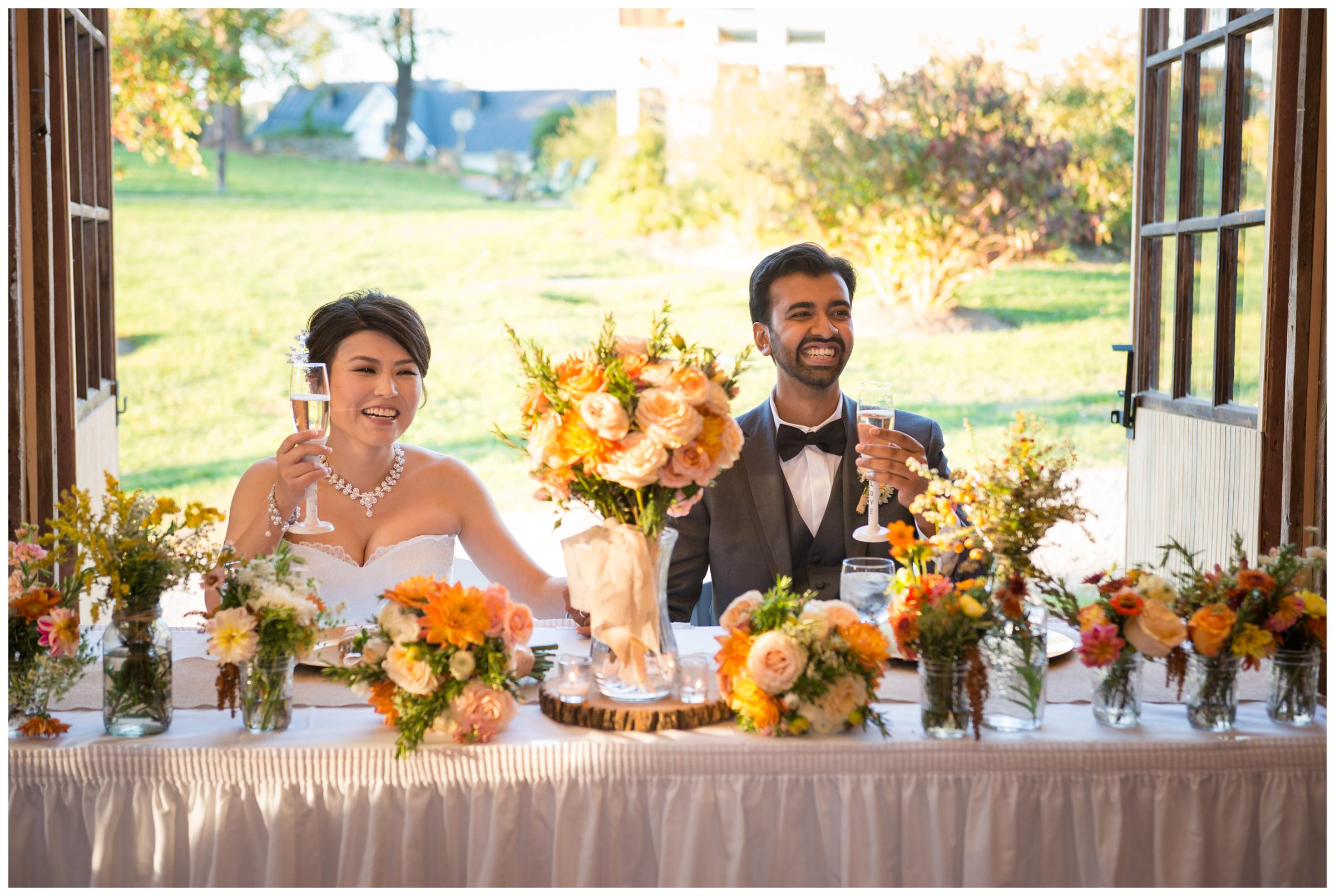 Bride and groom laugh during toasts at rustic barn wedding reception in Northern Virginia.