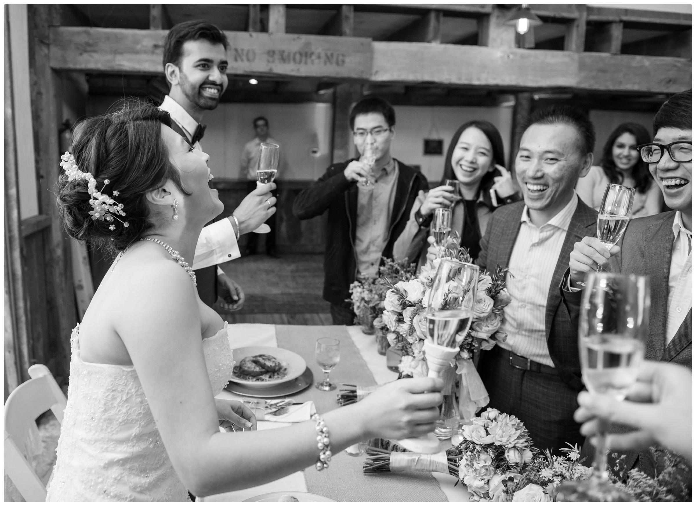 Newlyweds laugh with guests at rustic barn wedding.