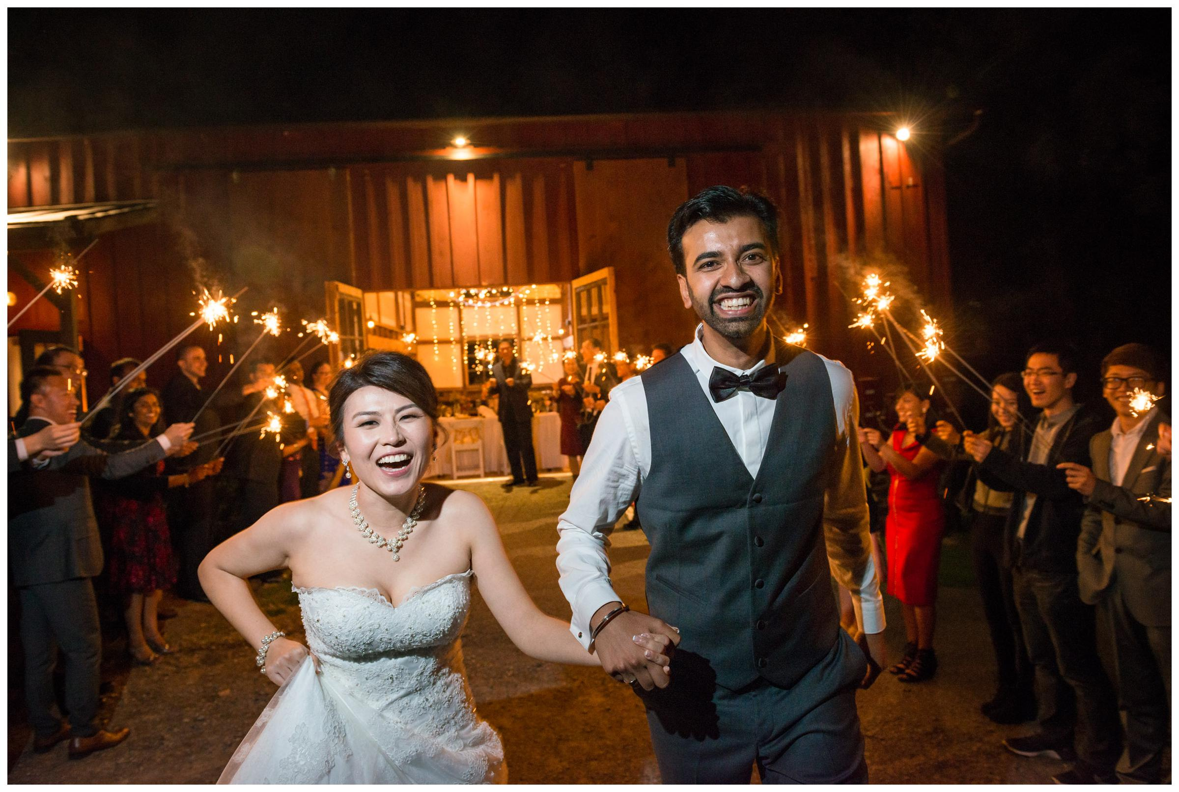 Bride and groom during sparkler wedding reception exit in rustic barn.