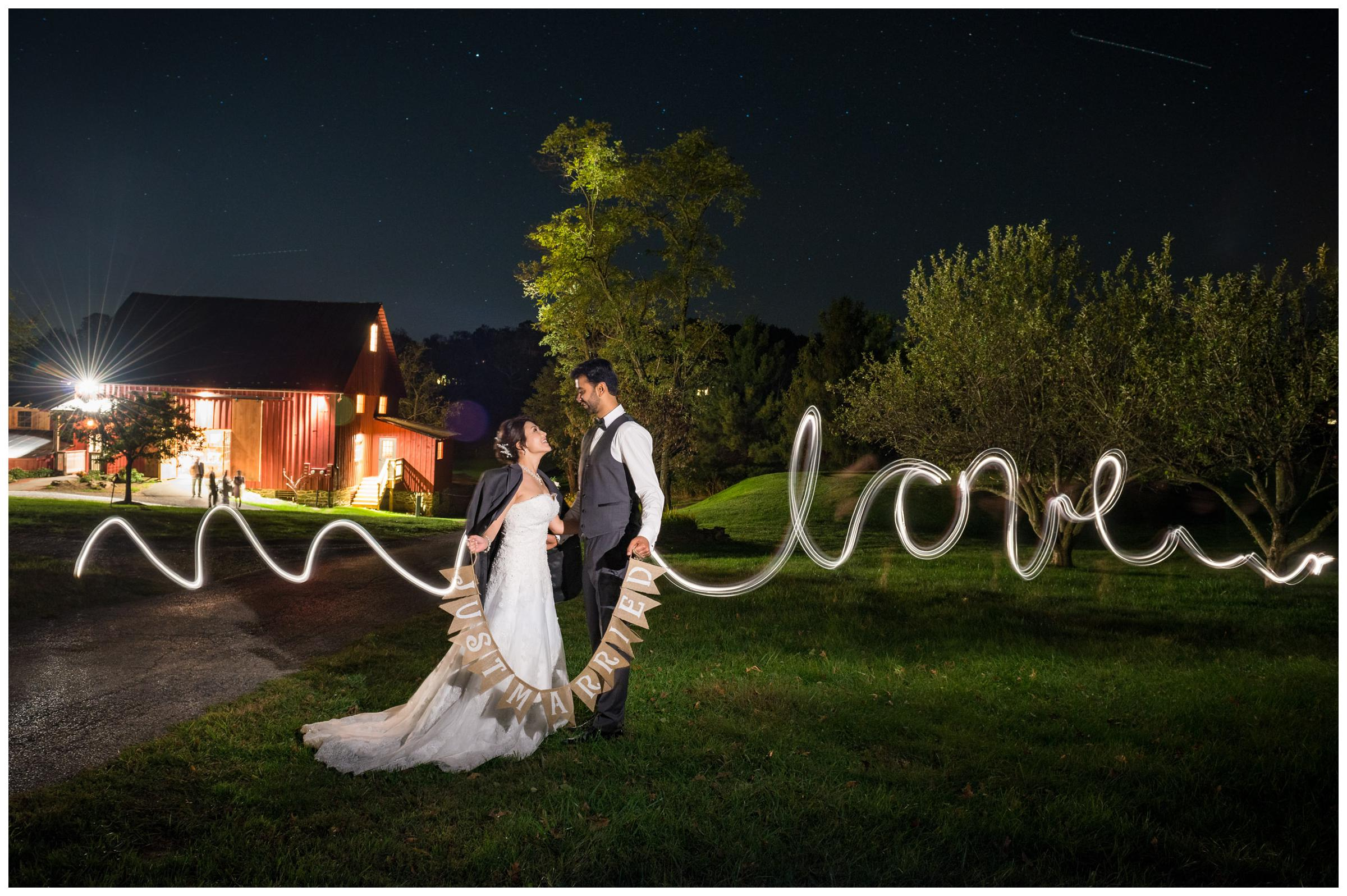 "Long exposure light painting photo with the word ""love"" after rustic barn wedding."