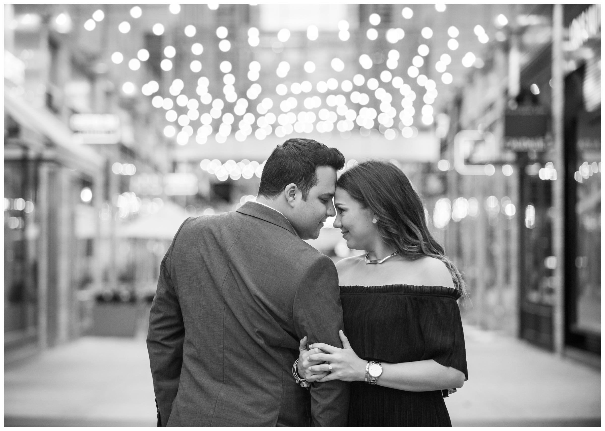 Couple surrounded by string lights during engagement session in City Center, Washington, D.C.
