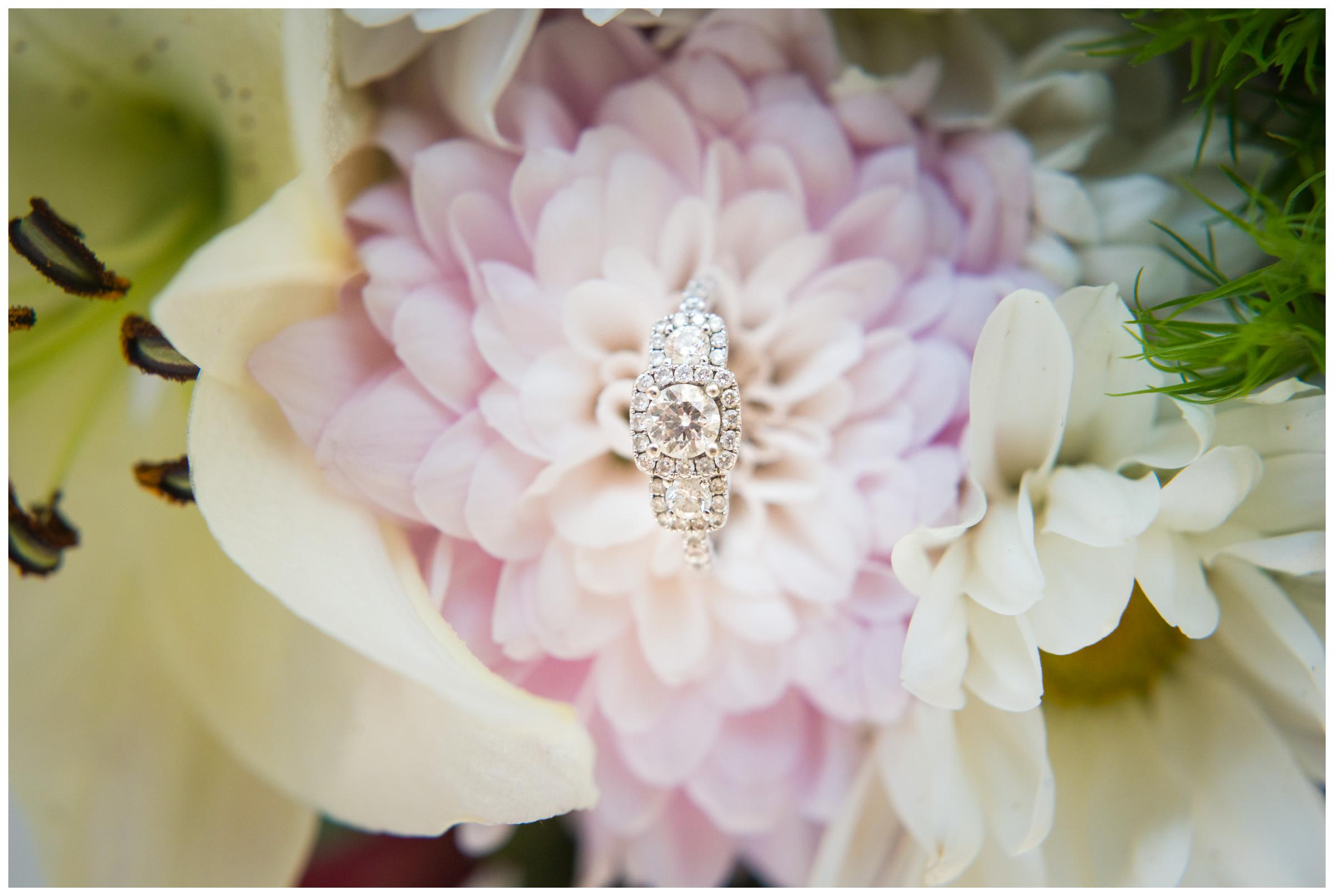 engagement ring sitting on pink flower