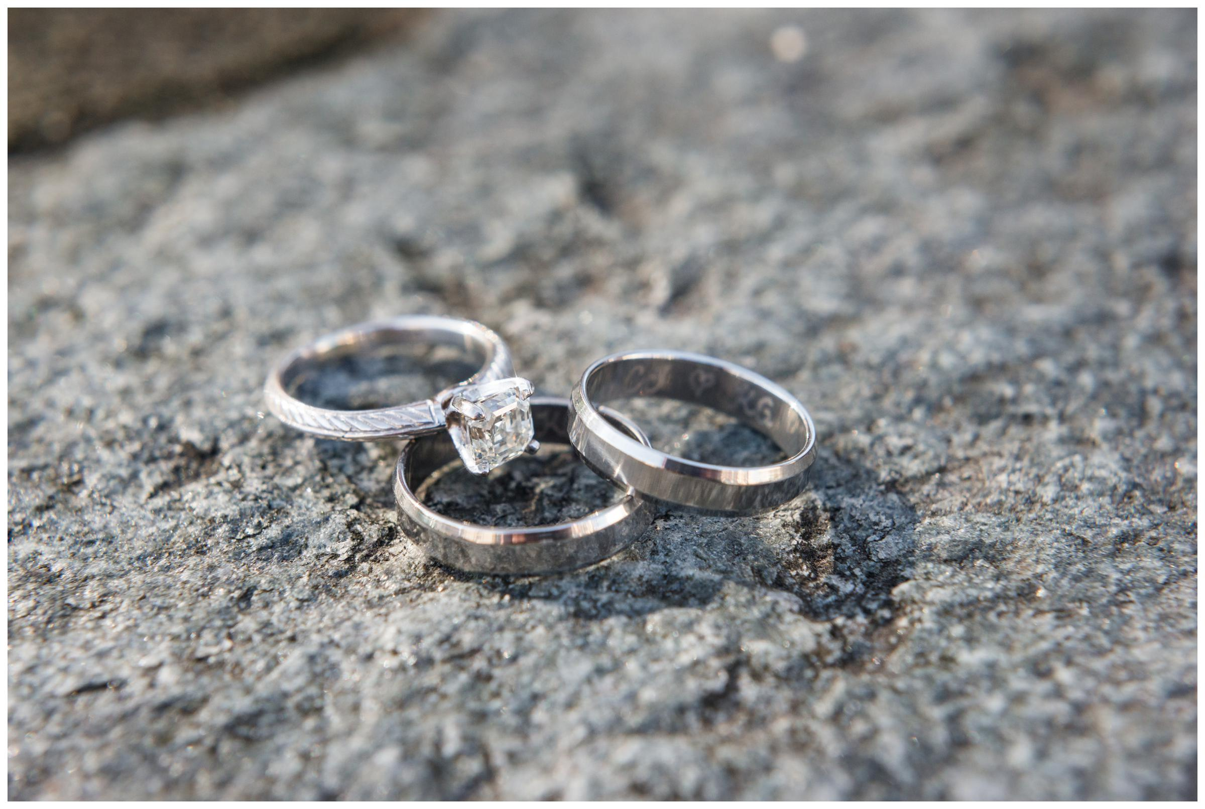 Engagement ring and engraved wedding rings on granite