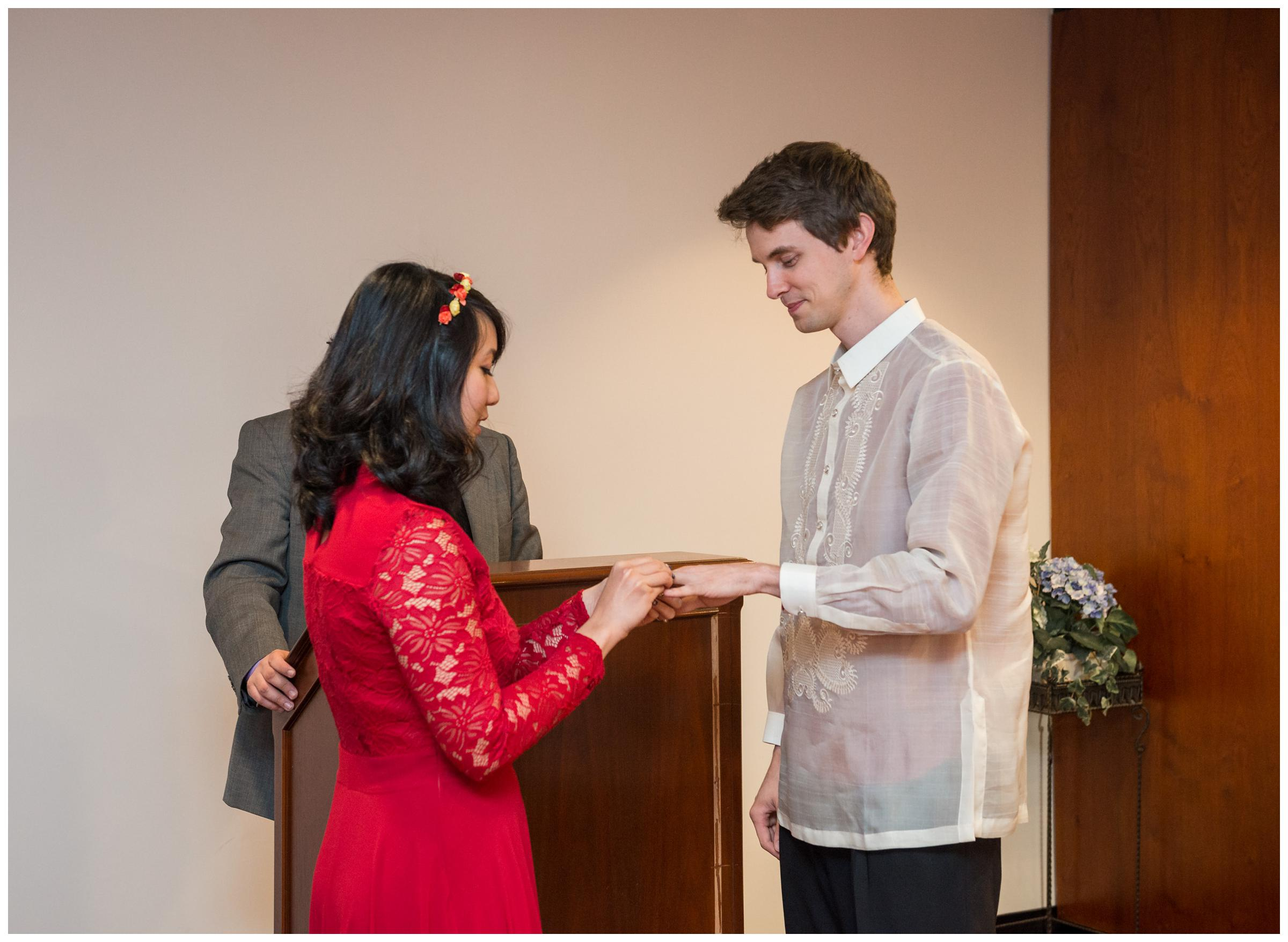 bride and groom exchanging rings during elopement wedding at Montgomery County Courthouse in Rockville, Maryland