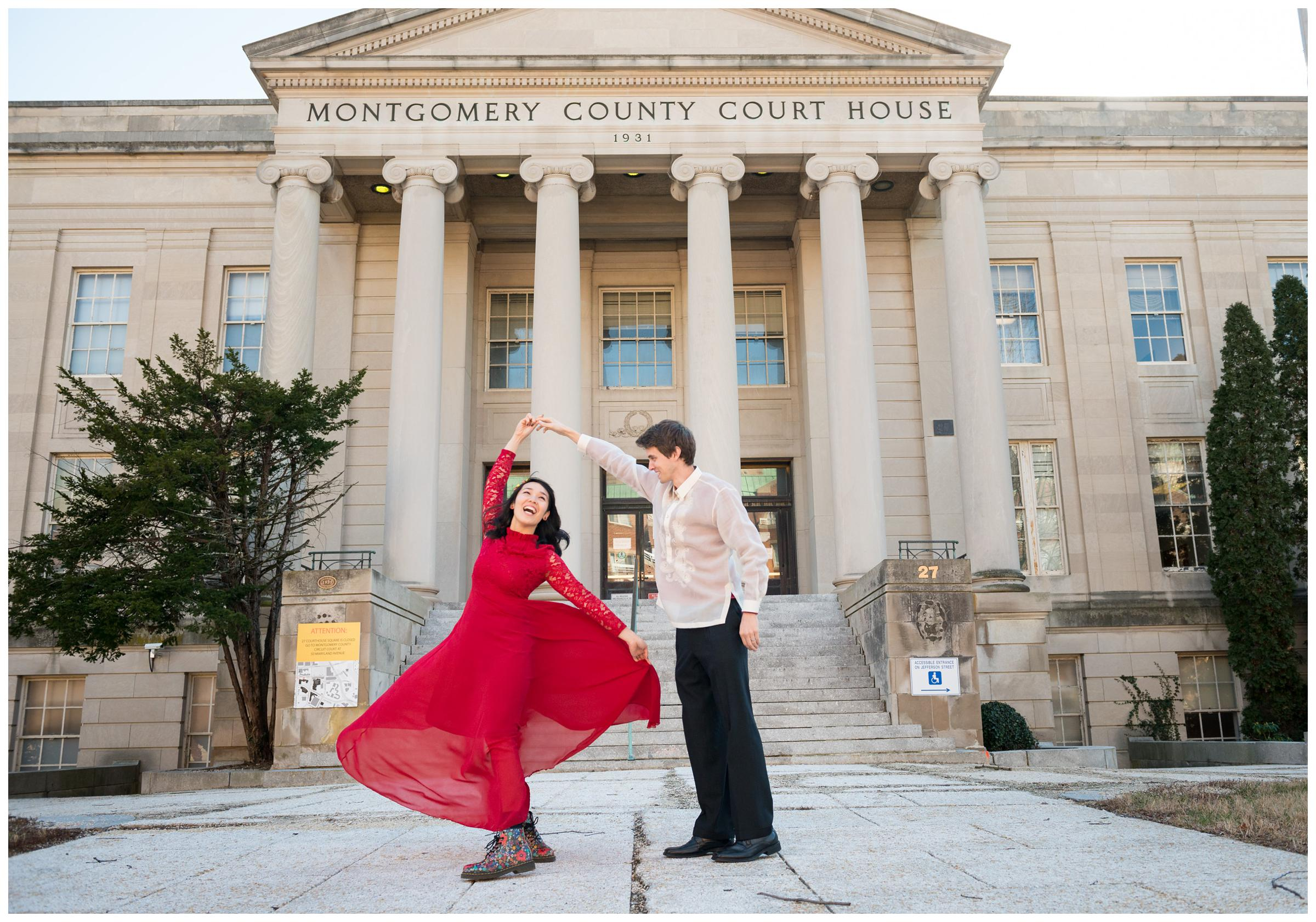 groom twirling bride in red dress outside of Montgomery County Courthouse after wedding